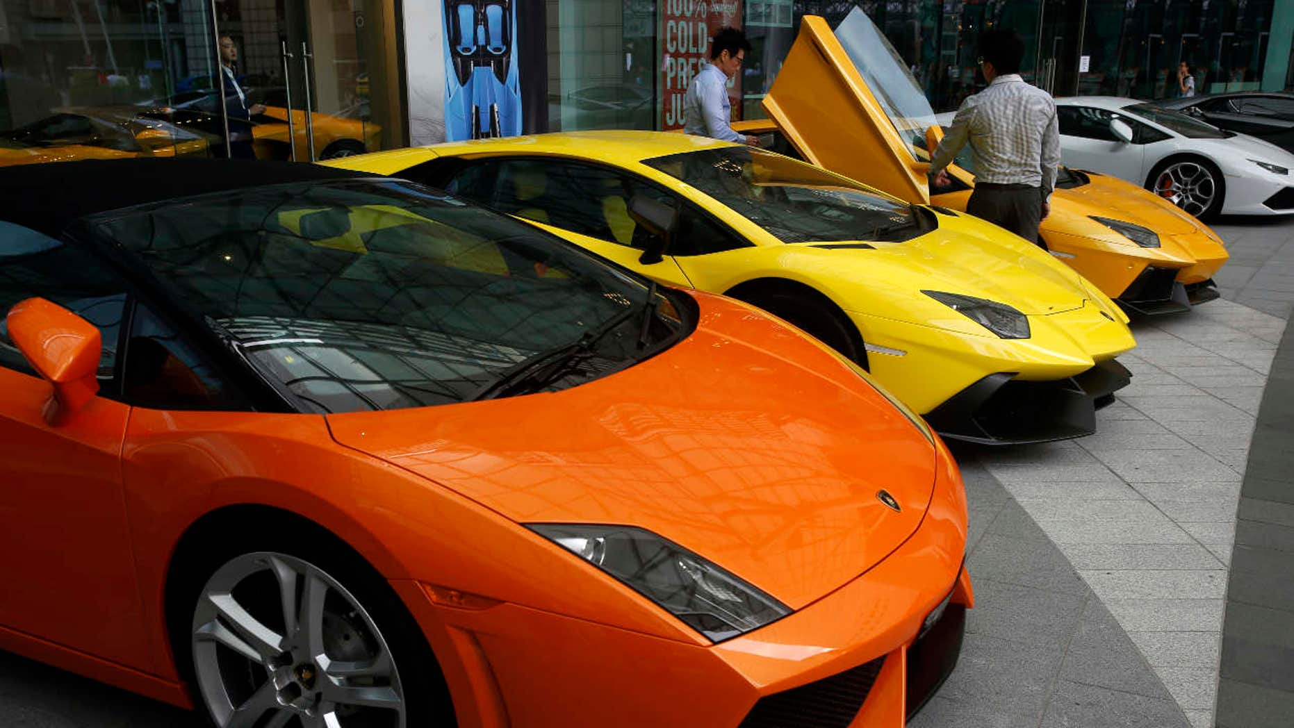 Men look at a Lamborghini car outside a showroom in Singapore's central business district.