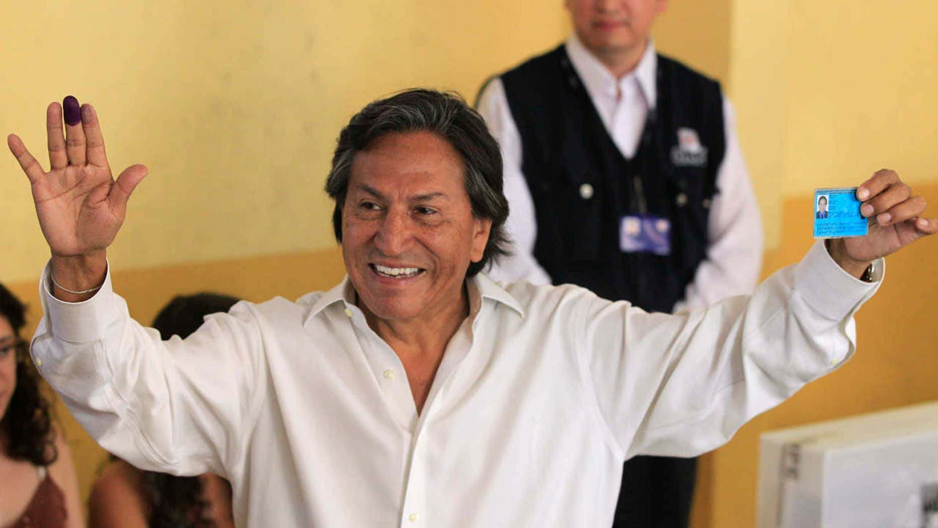 FILE -- In this April 10, 2011 file photo, then presidential candidate Alejandro Toledo holds up his ink-stained finger and identification card after voting in the general elections, in Lima, Peru.
