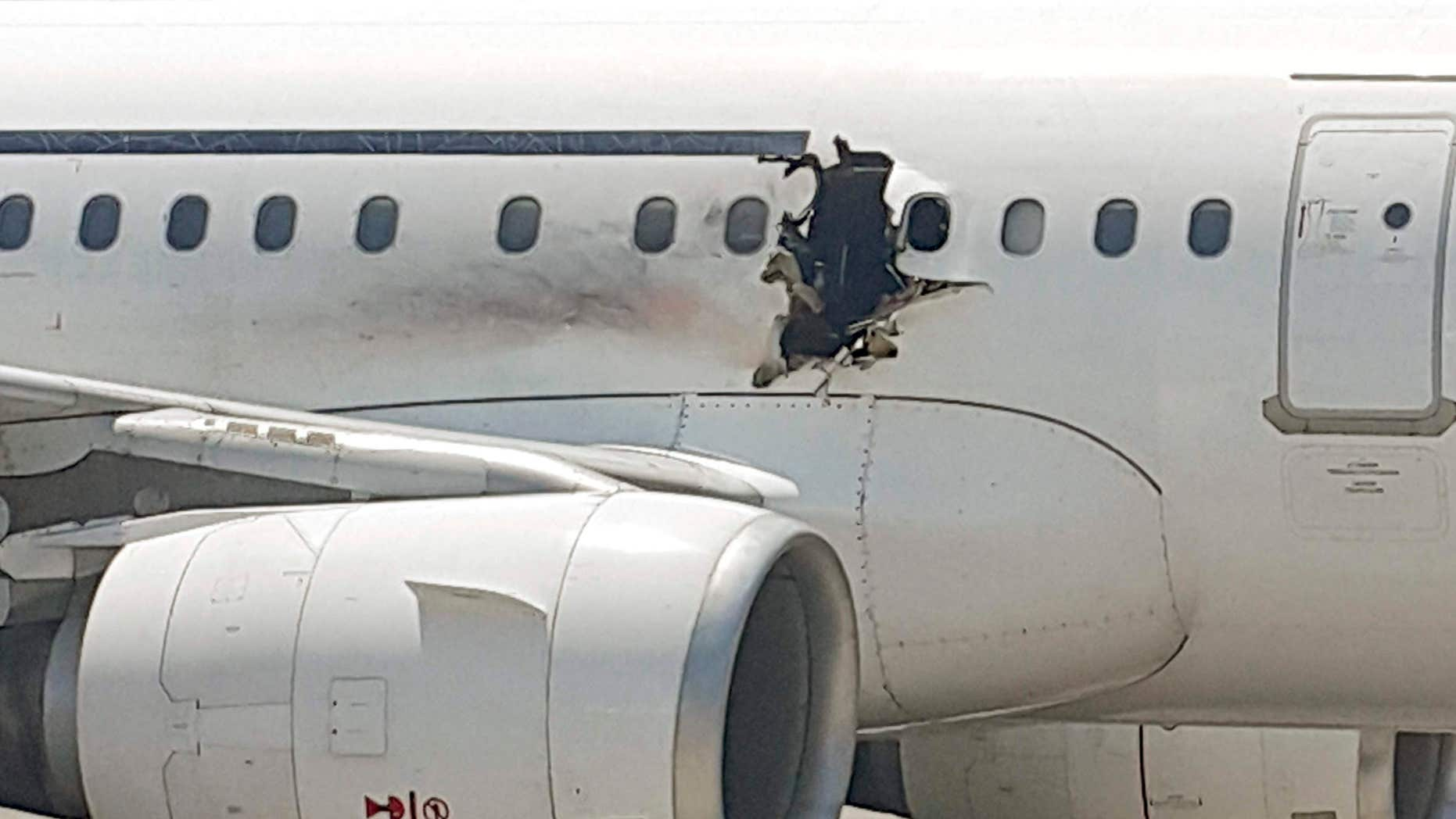 FILE - In this Tuesday, Feb. 2, 2016 file photo, a hole is photographed in a plane operated by Daallo Airlines as it sits on the runway of the airport in Mogadishu, Somalia.
