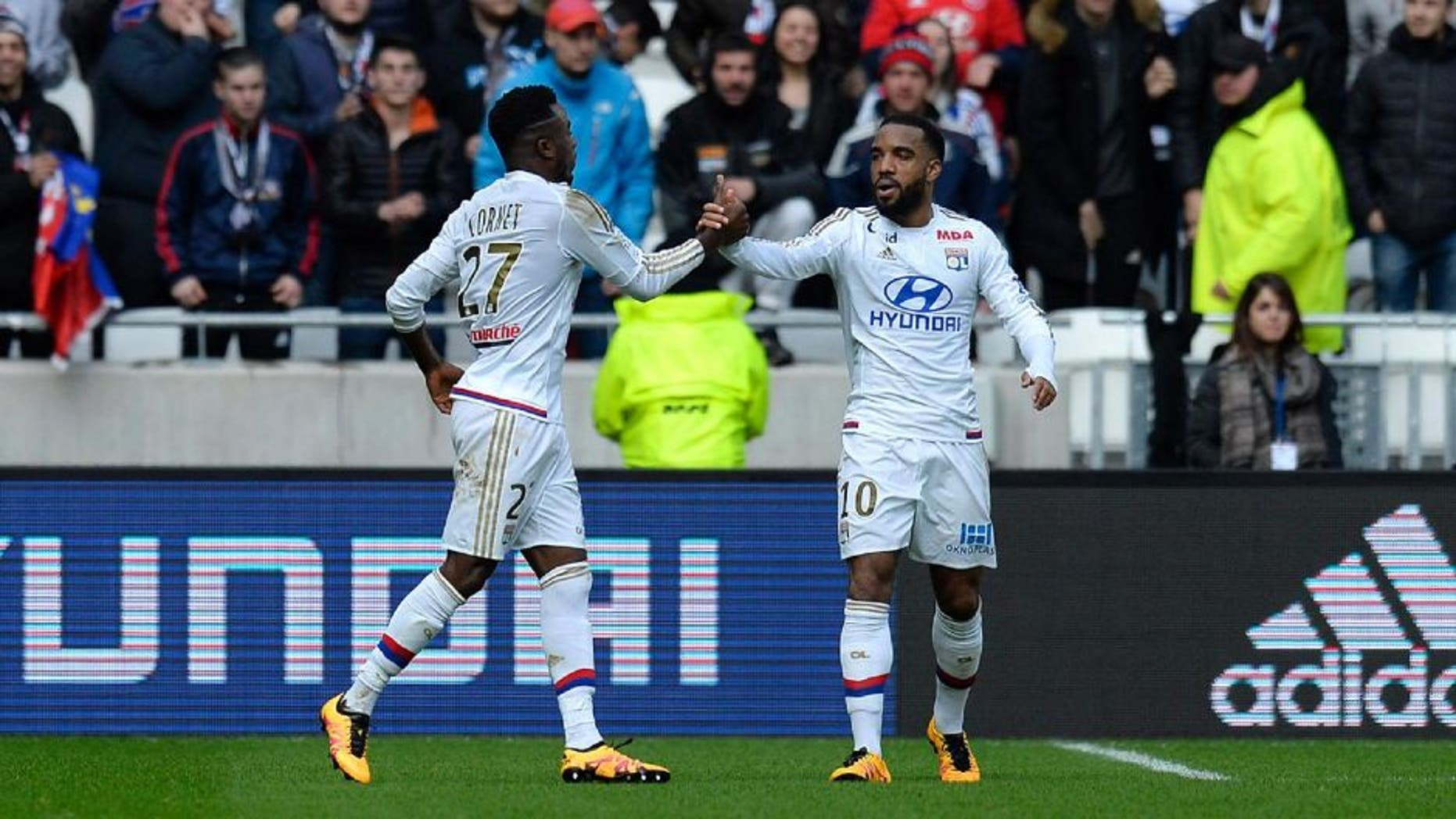 Lyon's French forward Maxwell Cornet (L) celebrates after scoring a goal with Lyon's French forward Alexandre Lacazette during the French L1 football match between Olympique Lyonnais (OL) and Stade Malherbe Caen (SMC) at the Parc Olympique Lyonnais stadium in Decines-Charpieu, central-eastern France on February 14, 2016. / AFP / ROMAIN LAFABREGUE (Photo credit should read ROMAIN LAFABREGUE/AFP/Getty Images)