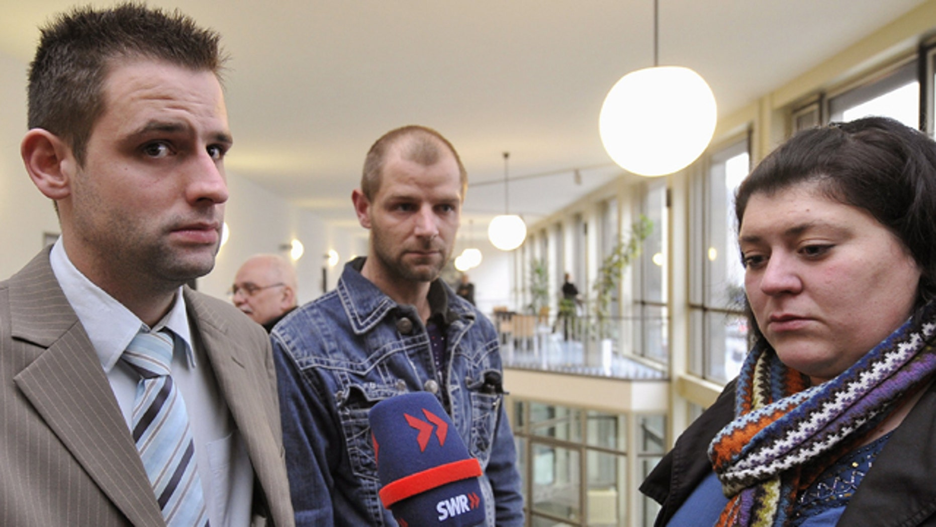 Feb. 15: Bjoern B., left, and Markus S., both stepsons of Detlef S., and B.'s wife Nadja, give interviews outside the courtroom in the regional court in Koblenz, western Germany.