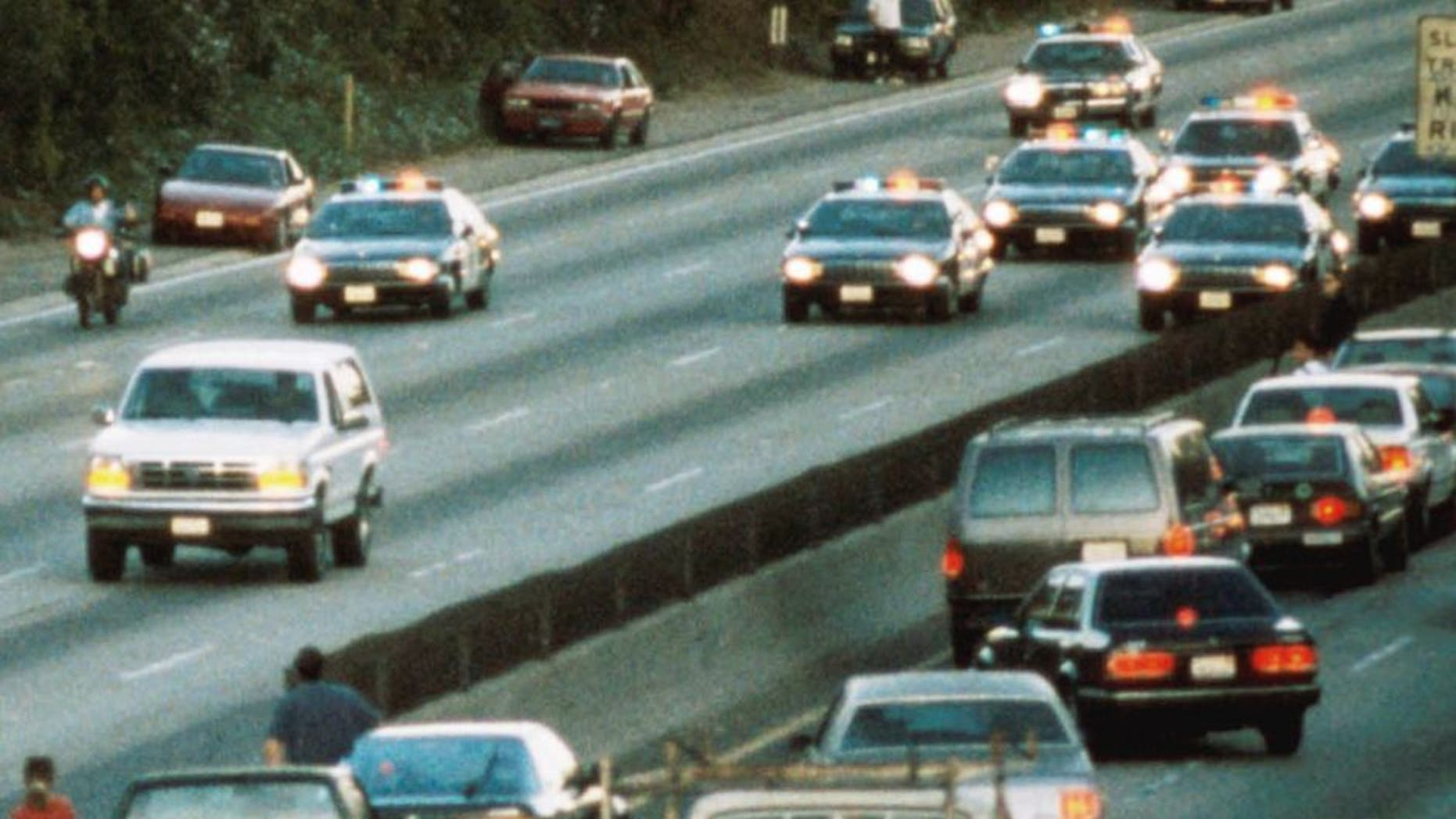 LOS ANGELES - JUNE 17: Motorists stop and wave as police cars pursue the Ford Bronco (white, R) driven by Al Cowlings, carrying fugitive murder suspect O.J. Simpson, on a 90-minute slow-speed car chase June 17, 1994 on the 405 freeway in Los Angeles, California. Simpson's friend Cowlings eventually drove Simpson home, with Simpson ducked under the back passenger seat, to Brentwood where he surrendered after a stand-off with police. (Photo by Jean-Marc Giboux/Liaison)