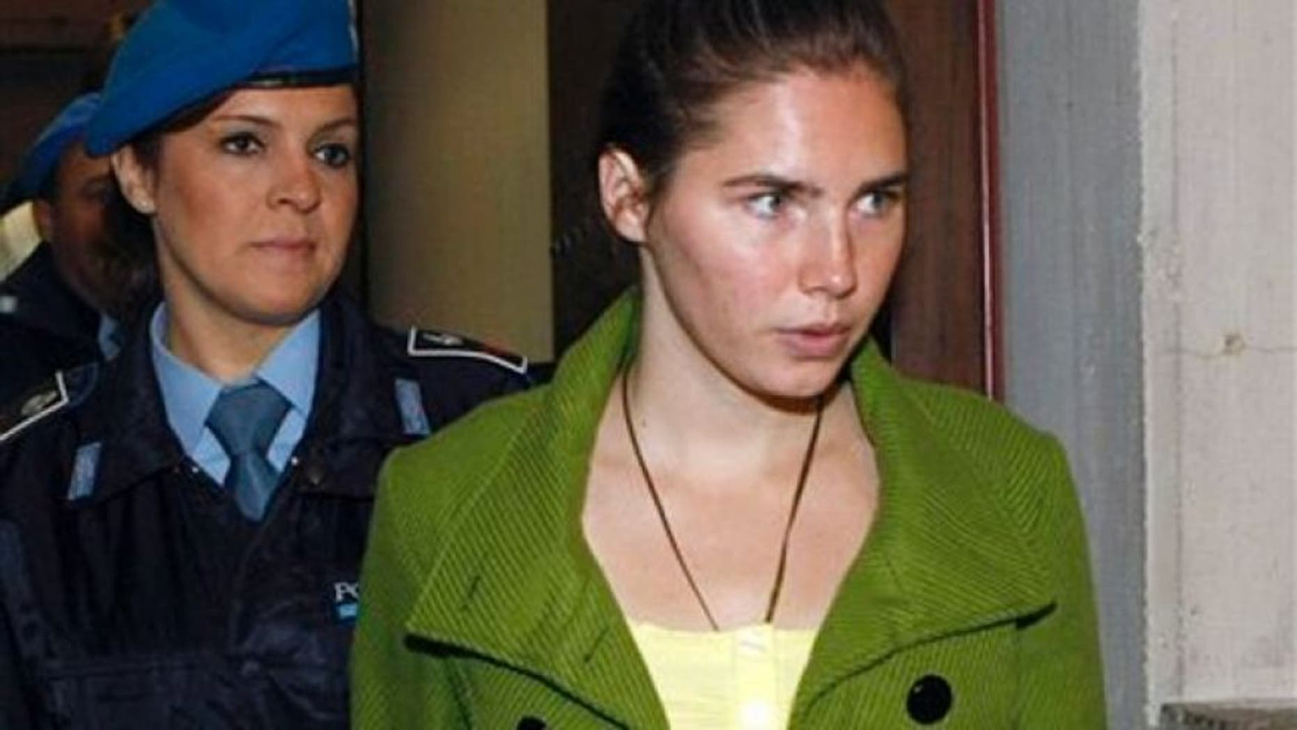 Dec. 4, 2009: Amanda Knox is accompanied by a penitentiary police officer prior to a final hearing at the court in Perugia, Italy. Knox was found guilty of murdering her British roommate Meredith Kercher.
