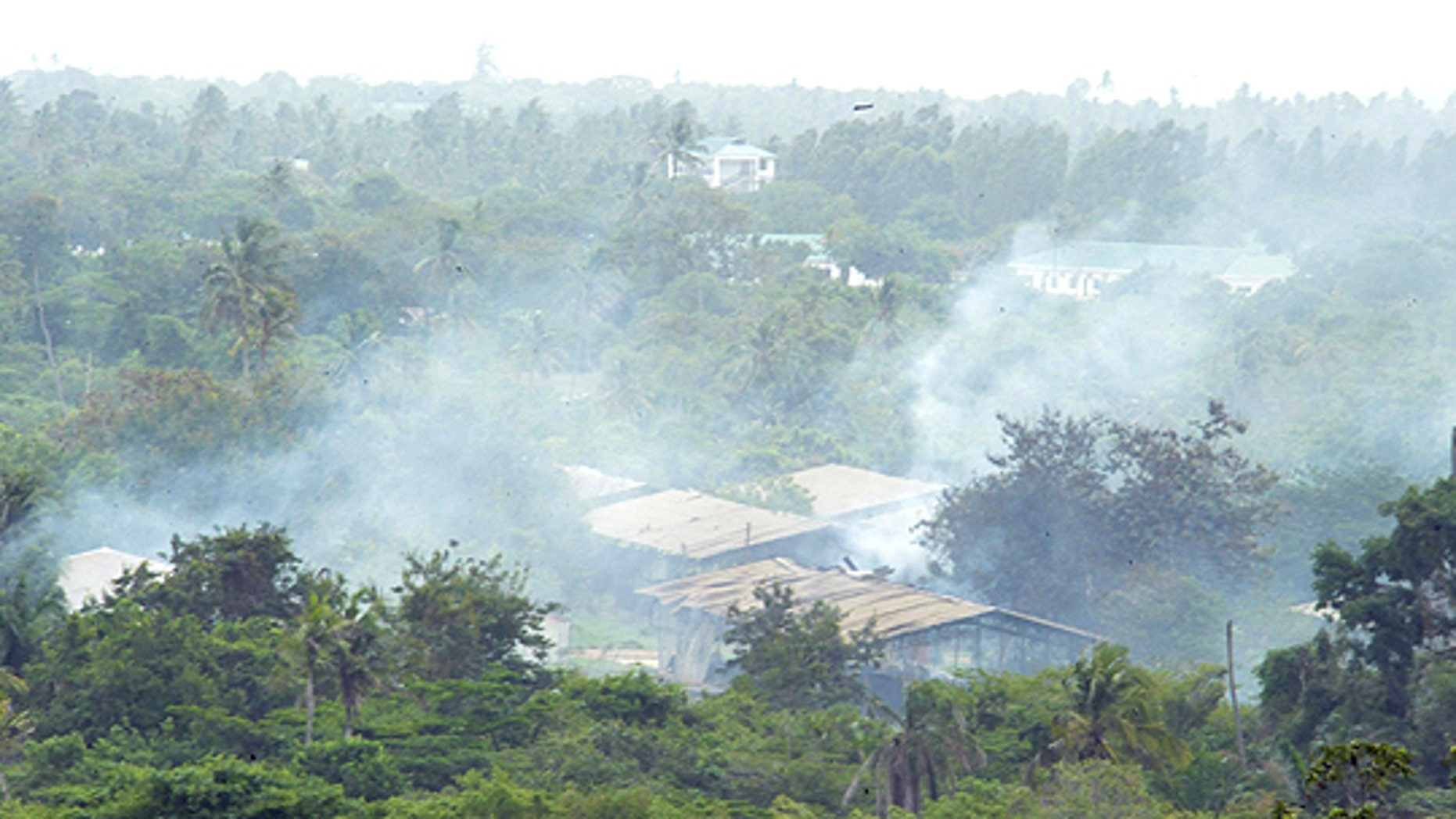 Feb. 17: Smoke drifts over the Gongolamboto military camp on the outskirts of Dar es Salaam following several explosions.