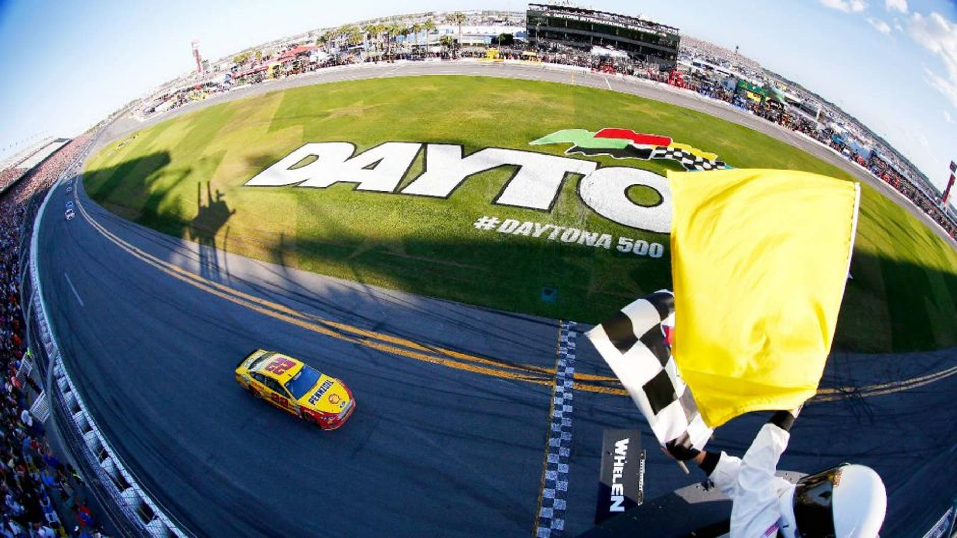 DAYTONA BEACH, FL - FEBRUARY 22: Joey Logano, driver of the #22 Shell Pennzoil Ford, takes the checkered flag to win the NASCAR Sprint Cup Series 57th Annual Daytona 500 at Daytona International Speedway on February 22, 2015 in Daytona Beach, Florida. (Photo by Jonathan Ferrey/NASCAR via Getty Images)