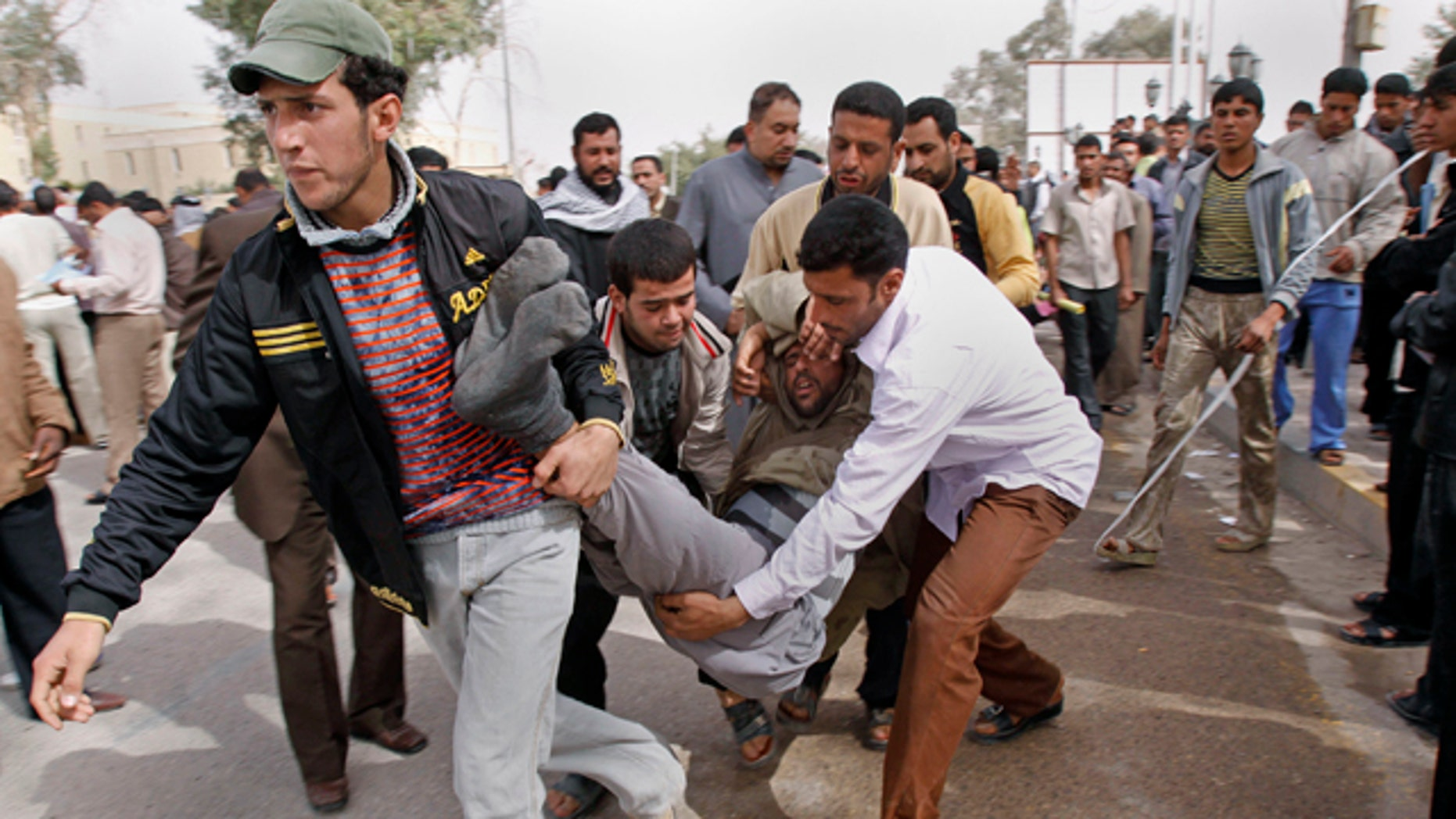 Iraqi anti-government protesters carry a man who collapsed during a demonstration in Basra, Iraq's second-largest city, 550 kilometers (340 miles) southeast of Baghdad, Iraq, Thursday, Feb. 17, 2011. Hundreds of Iraqi demonstrators massed Thursday in the southern city of Basra to demand the local governor's ouster while protesters elsewhere stormed a local government building, the latest examples of the anger sweeping the country over poor government services and high unemployment. (AP Photo/Nabil al-Jurani)