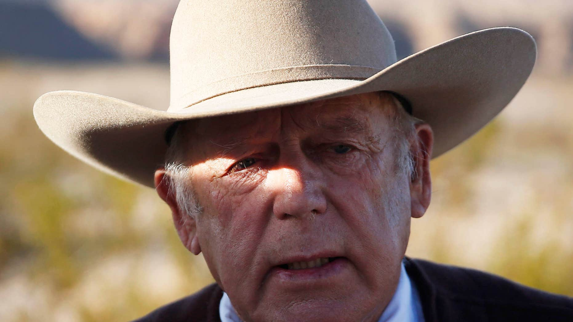 FILE - In a Wednesday, Jan. 27, 2016 file photo, rancher Cliven Bundy speaks to media while standing along the road near his ranch, in Bunkerville, Nev.