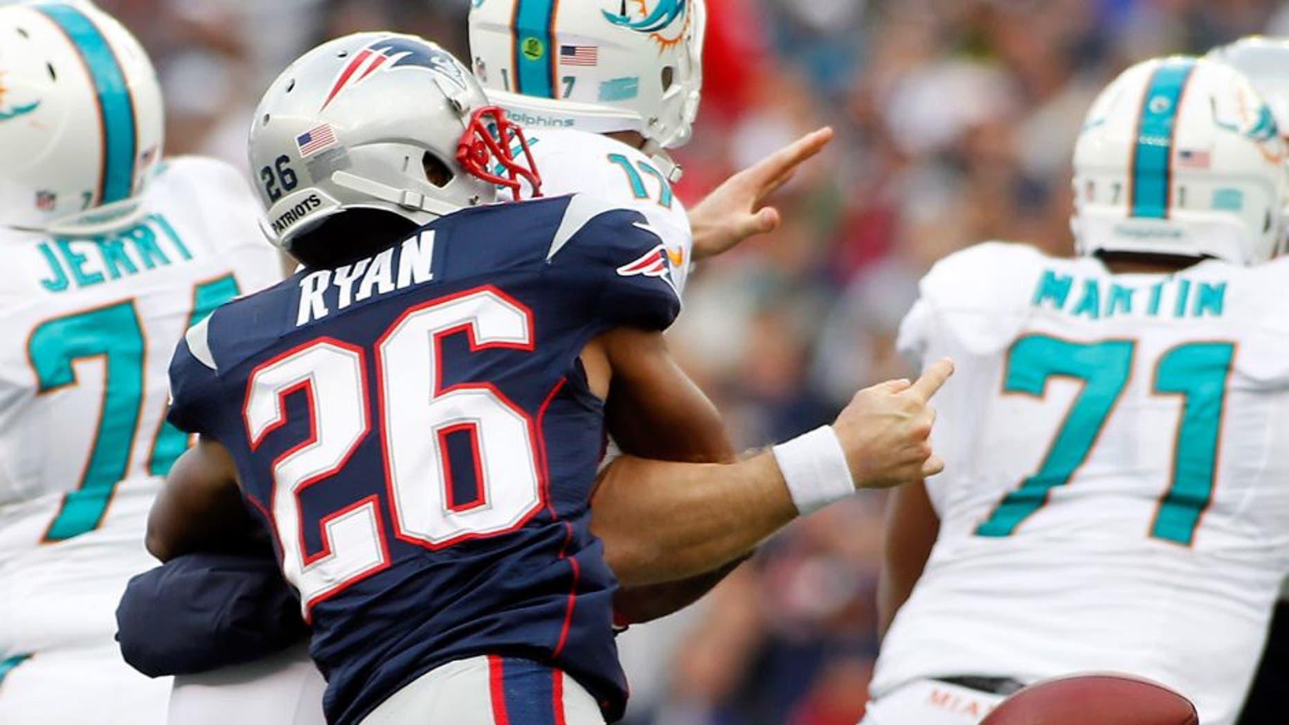 Oct 27, 2013; Foxborough, MA, USA; New England Patriots cornerback Logan Ryan (26) strip sacks Miami Dolphins quarterback Ryan Tannehill (17) during the third quarter at Gillette Stadium. Mandatory Credit: Stew Milne-USA TODAY Sports