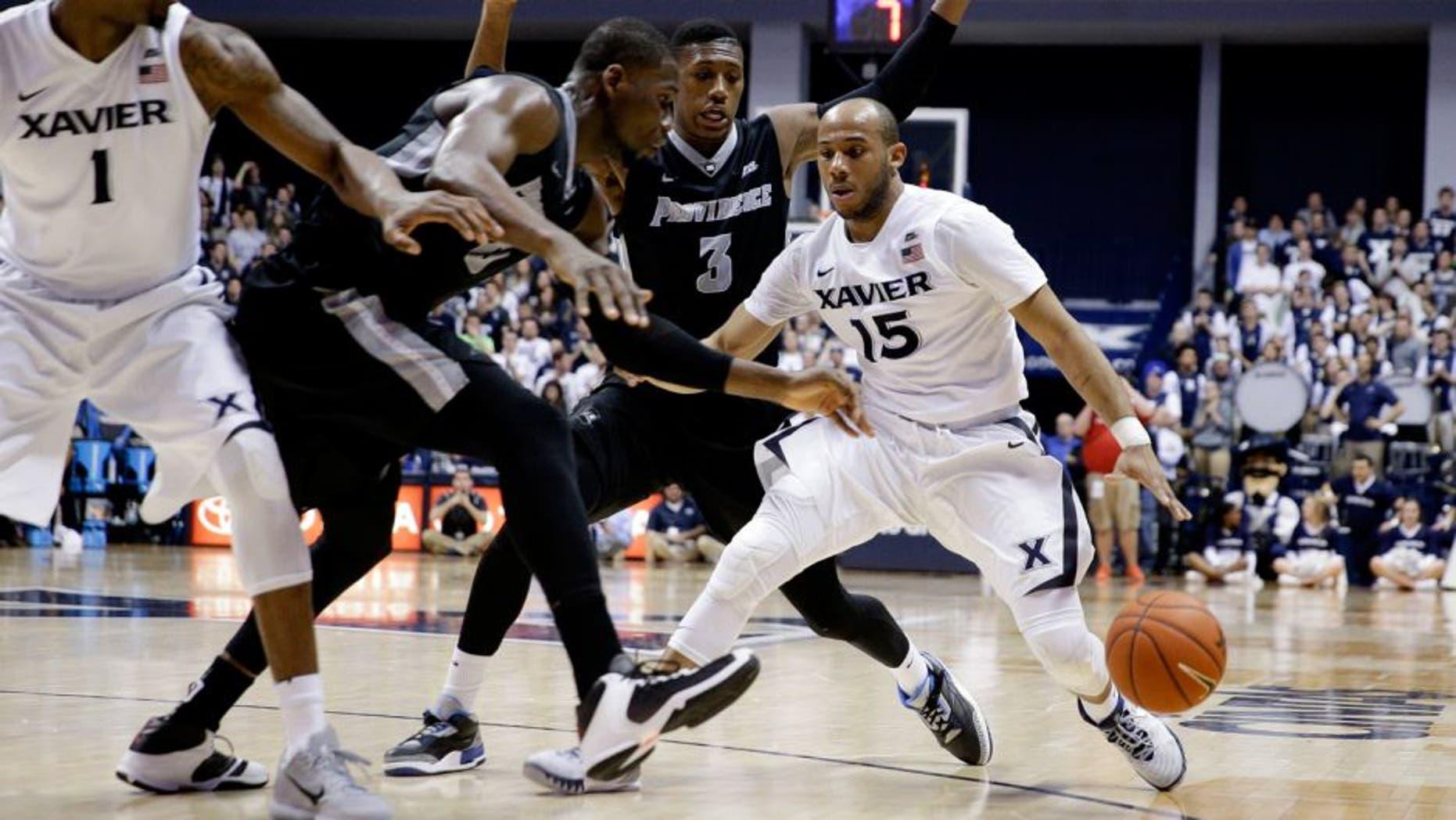 Xavier's Myles Davis (15) drives against Providence's Kris Dunn (3) and Kris Dunn, second from left, during the second half of an NCAA college basketball game Wednesday, Feb. 17, 2016, in Cincinnati. Xavier won 85-74. (AP Photo/John Minchillo)