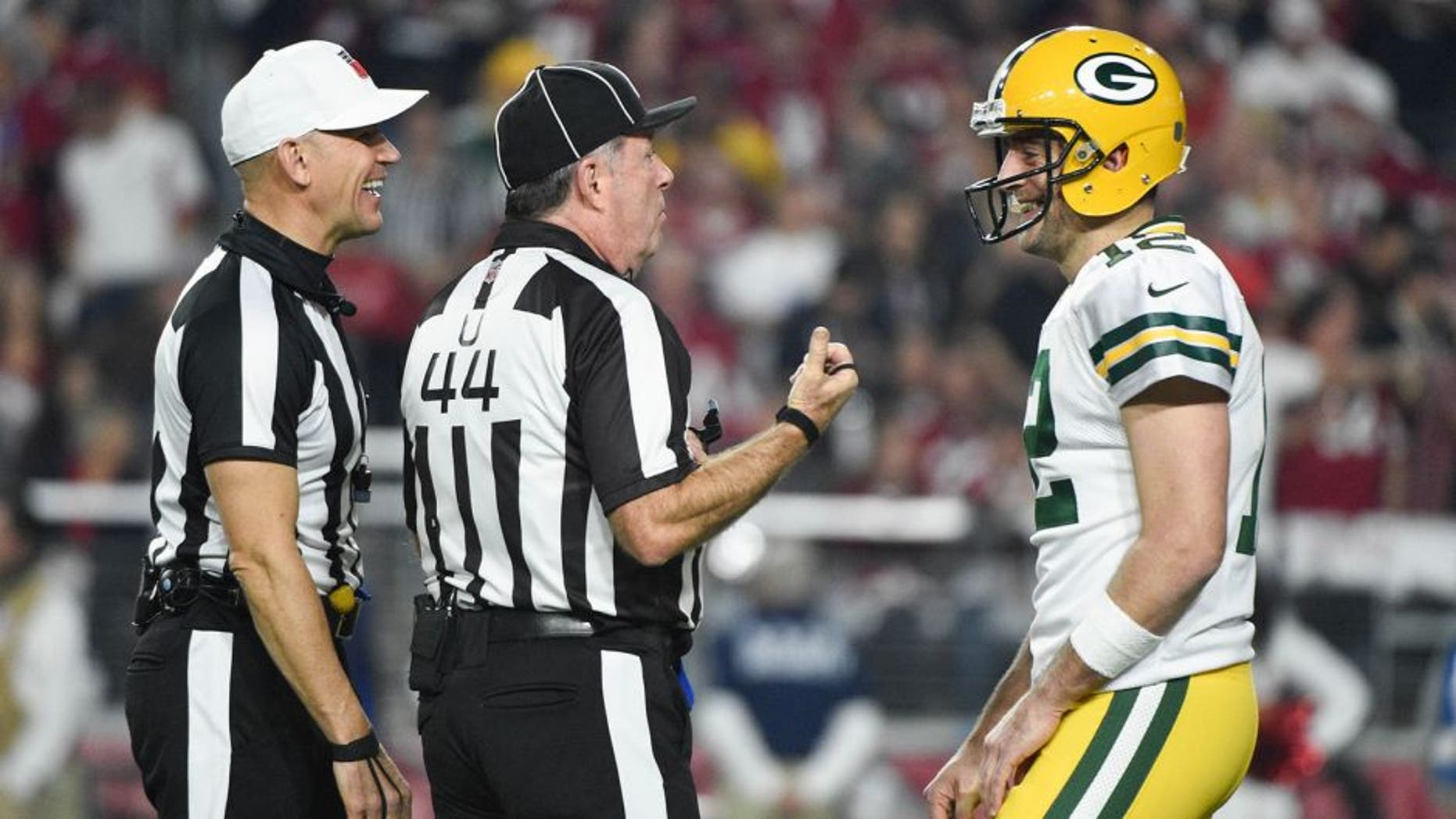 January 16, 2016; Glendale, AZ, USA; Green Bay Packers quarterback Aaron Rodgers (12) talks to NFL referee Clete Blakeman (34, left) and umpire Jeff Rice (44) during the first quarter in a NFC Divisional round playoff game against the Arizona Cardinals at University of Phoenix Stadium. The Cardinals defeated the Packers 26-20 in overtime. Mandatory Credit: Kyle Terada-USA TODAY Sports