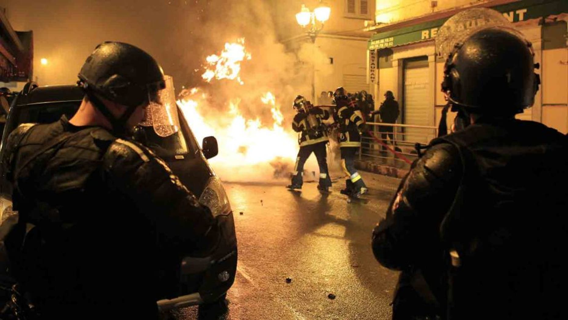 """Firefighters try to extinguish a fire during clashes between protesters and police in Corte on the French Mediterranean island of Corsica on February 16, 2016. French club Bastia have """"categorically refused"""" an order by the French Professional League (LFP) to advance the kick-off time of their Ligue 1 game against Nantes on February 20 amid security fears in Corsica. The decision to bring the game forward from 20:00 local time (1900GMT) to 14:00 (1300GMT) was requested by police on the French Mediterranean island after violence sparked by Corsican fans during the league game at Reims on February 13. Fans threw fireworks at police before and after the match in the Champagne region with the violence spilling into the town when a 22-year-old Corsican suffered a serious eye injury while being pursued by police. Fresh clashes erupted on Tuesday when around 50 masked individuals interrupted peaceful demonstrations by throwing Molotov cocktails at police forces, who in turn responded with tear gas to quell the trouble. / AFP / Pascal POCHARD-CASABIANCA (Photo credit should read PASCAL POCHARD-CASABIANCA/AFP/Getty Images)"""