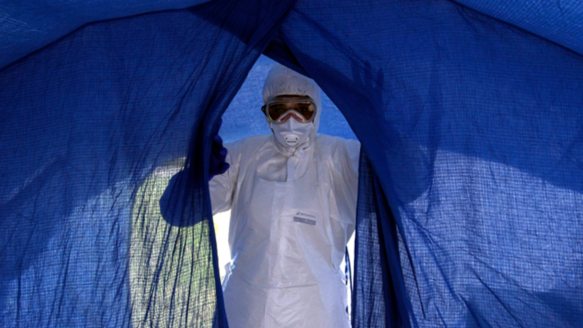 In this Sept. 24, 2014 photo, nurse Dalila Martinez, trainer of the Cuban medical team to travel to Sierra Leone, enters a tent during a practice drill at a training camp, in Havana, Cuba. Cuba's health ministry is sending more than 160 health workers to help stop the raging Ebola outbreak in Sierra Leone in early October. They will stay for six months. (AP Photo/Ladyrene Perez, Cubadebate)
