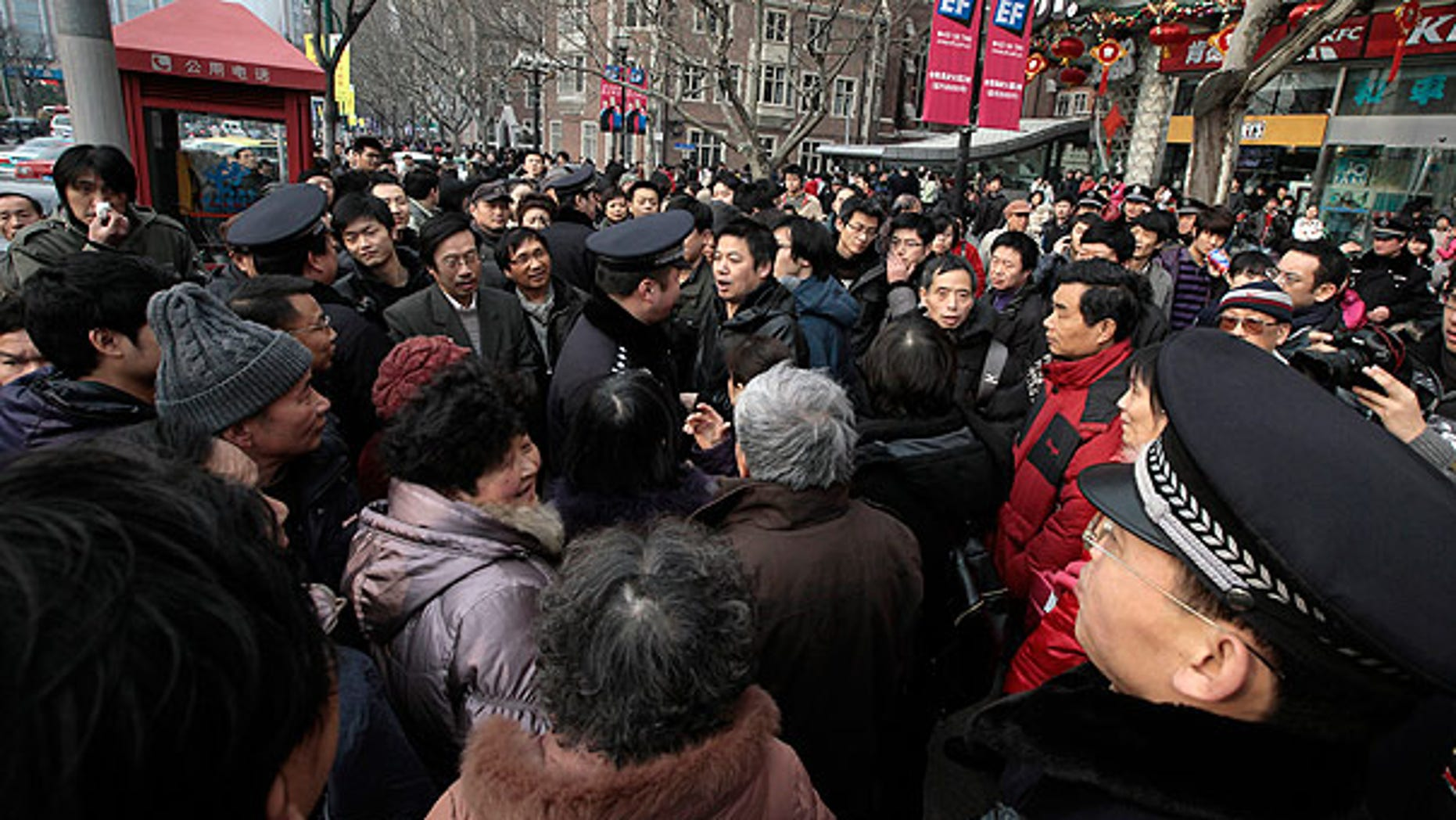 Feb. 20: Police officers urge people to leave as they gather in front of a cinema that was a planned protest site in Shanghai, China.