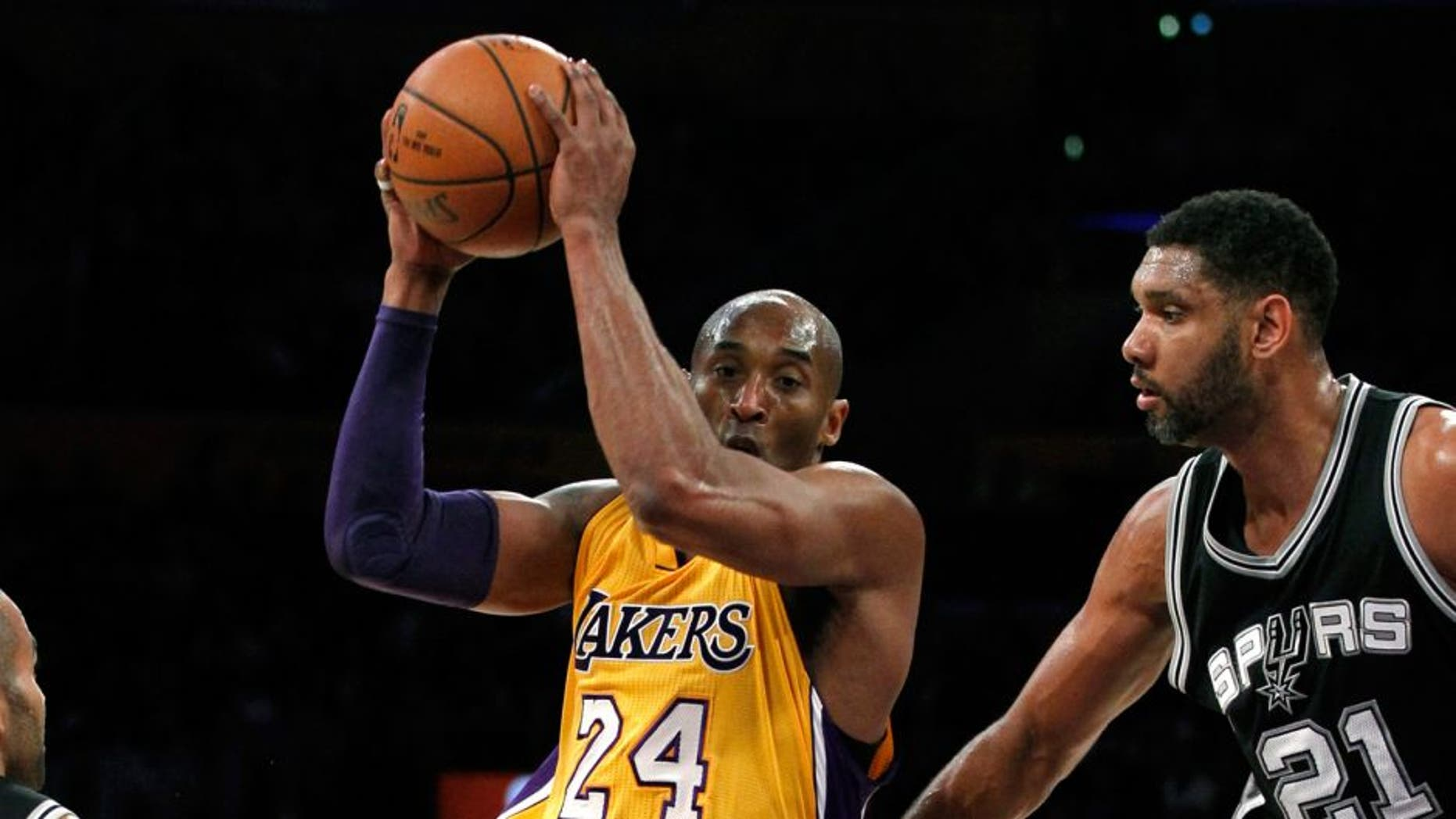 Los Angeles Lakers forward Kobe Bryant (24) drives the lane against San Antonio Spurs guard Tony Parker (9) and center Tim Duncan (21) during the first half of an NBA basketball game in Los Angeles, Friday, Feb. 19, 2016. (AP Photo/Alex Gallardo)