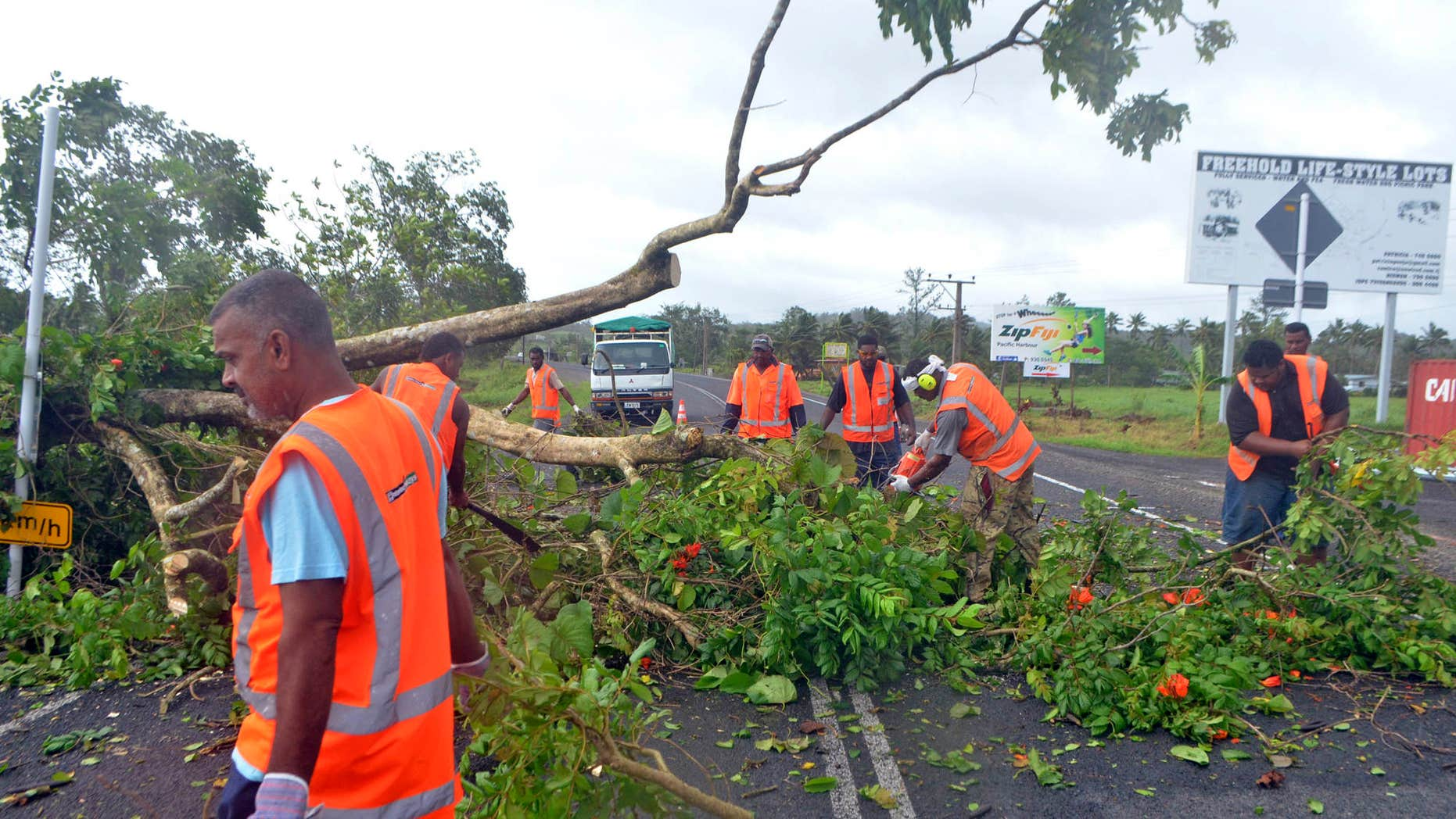 Road workers remove a fallen tree blocking a road near Lami, Fiji, Sunday, Feb. 21, 2016, after cyclone Winston ripped through the country.