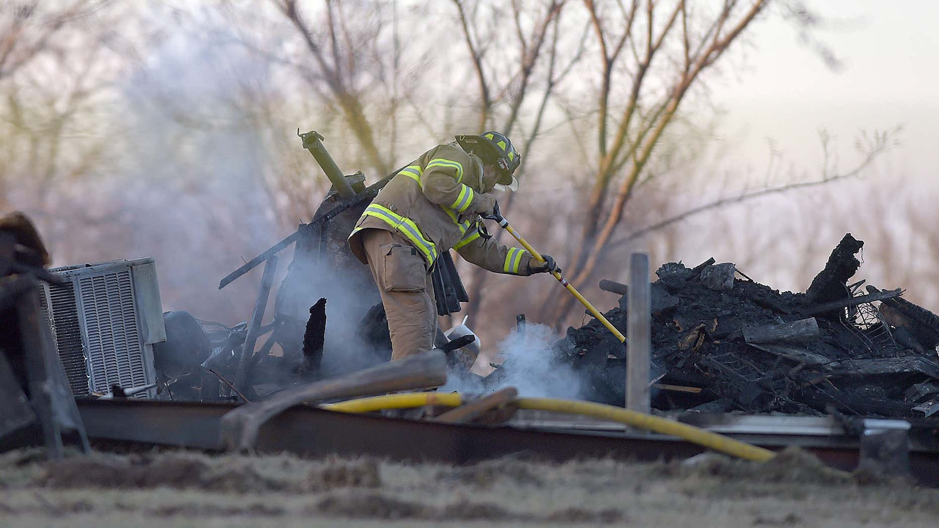 Feb. 20, 2016: A firefighter puts out a hot spot at the home 4170 Buena Vista Road in Edgerton, Mo.