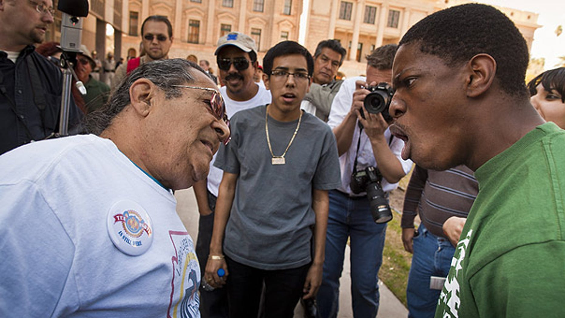 Feb. 22: A supporter and opponent of illegal immigrant birthrights debate at the State Capitol in Phoenix.