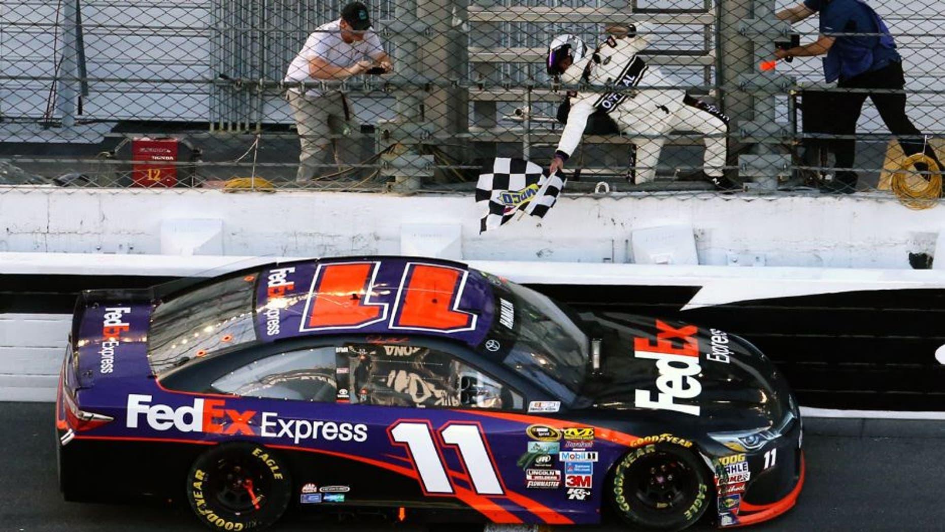Danny Hamlin picks up the checkered flag after winning the Daytona 500 at Daytona International Speedway in Daytona Beach, Fla., on Sunday, Feb. 21, 2016. (Joe Burbank/Orlando Sentinel/TNS via Getty Images)