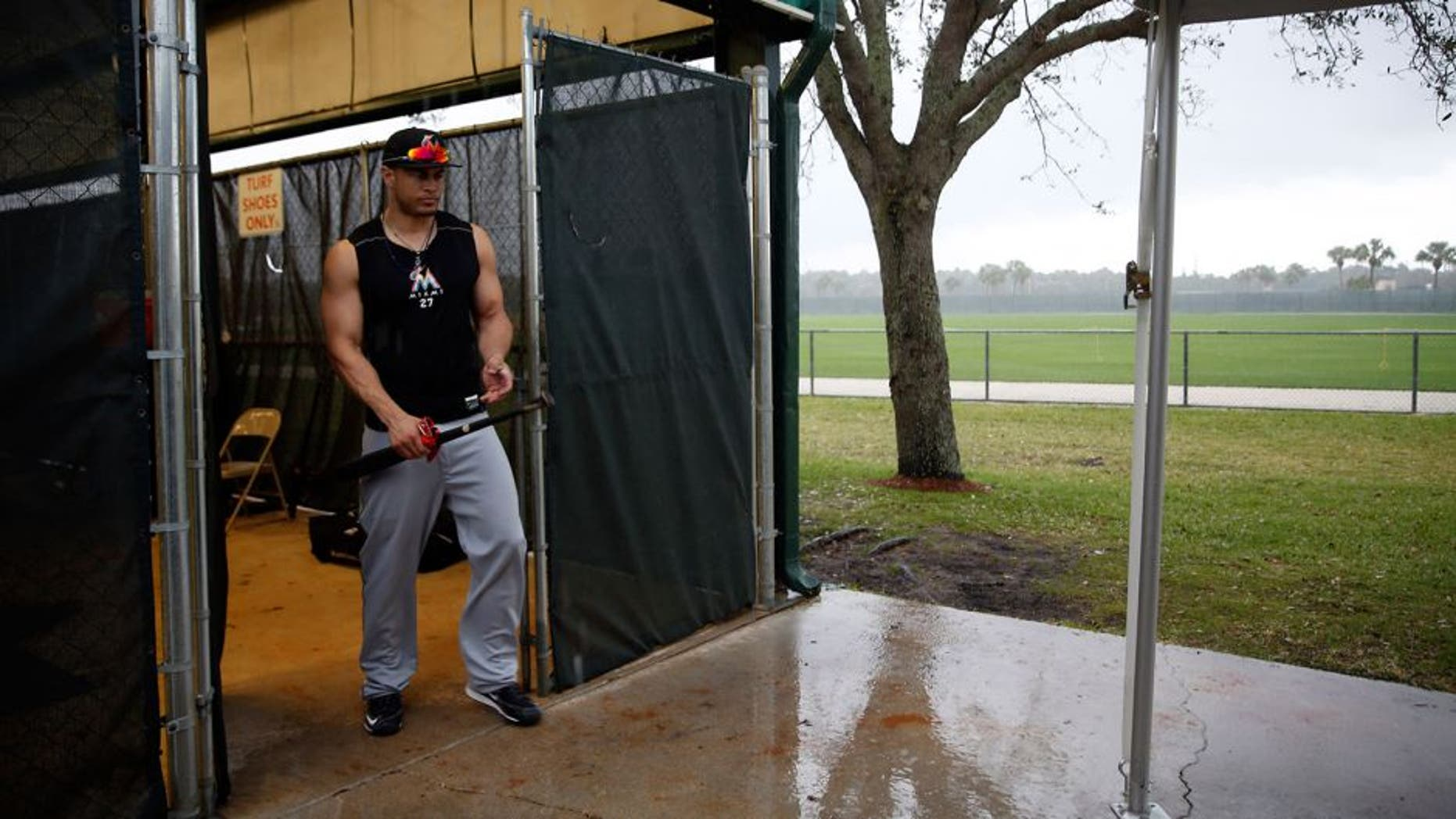 Miami Marlins' Giancarlo Stanton steps out of a batting cage as a steady rain falls during spring training baseball practice Tuesday, Feb. 23, 2016, in Jupiter, Fla. (AP Photo/Jeff Roberson)