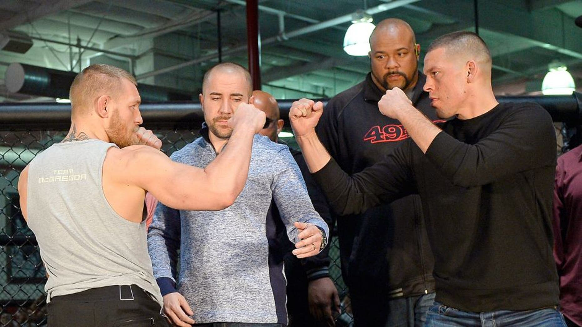 TORRANCE, CA - FEBRUARY 24: UFC featherweight champion Conor McGregor (L) and lightweight contender Nate Diaz (R) are held apart by Dave Sholler (2nd L), UFC vice president of public relations, after a news conference at UFC Gym February 24, 2016, in Torrance, California. (Photo by Kevork Djansezian/Getty Images)