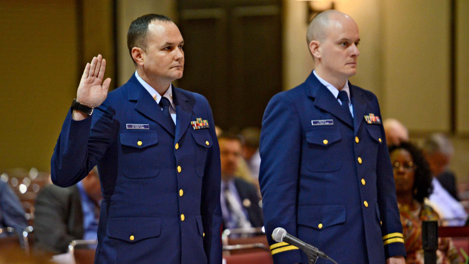 Feb. 24, 2016: OS2 Matthew Chancery, left, U.S. Coast Guard District 7, is sworn in to start the day while standing next to his counsel Lt. Travis Noyes as a U.S. Coast Guard investigative hearing into the sinking of the El Faro continues in Jacksonville, Fla..