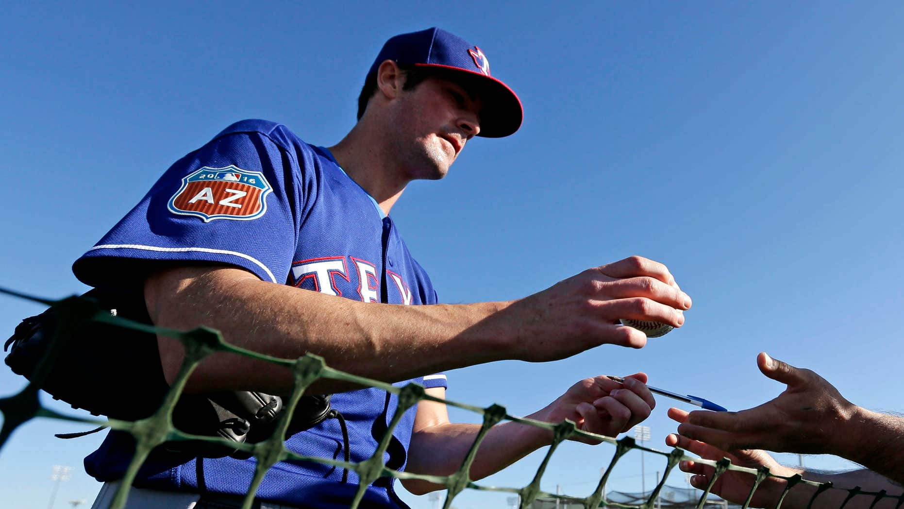FILE - In this Feb. 21, 2016, file photo, Texas Rangers pitcher Cole Hamels signs autographs during spring training baseball practice, in Surprise, Ariz.