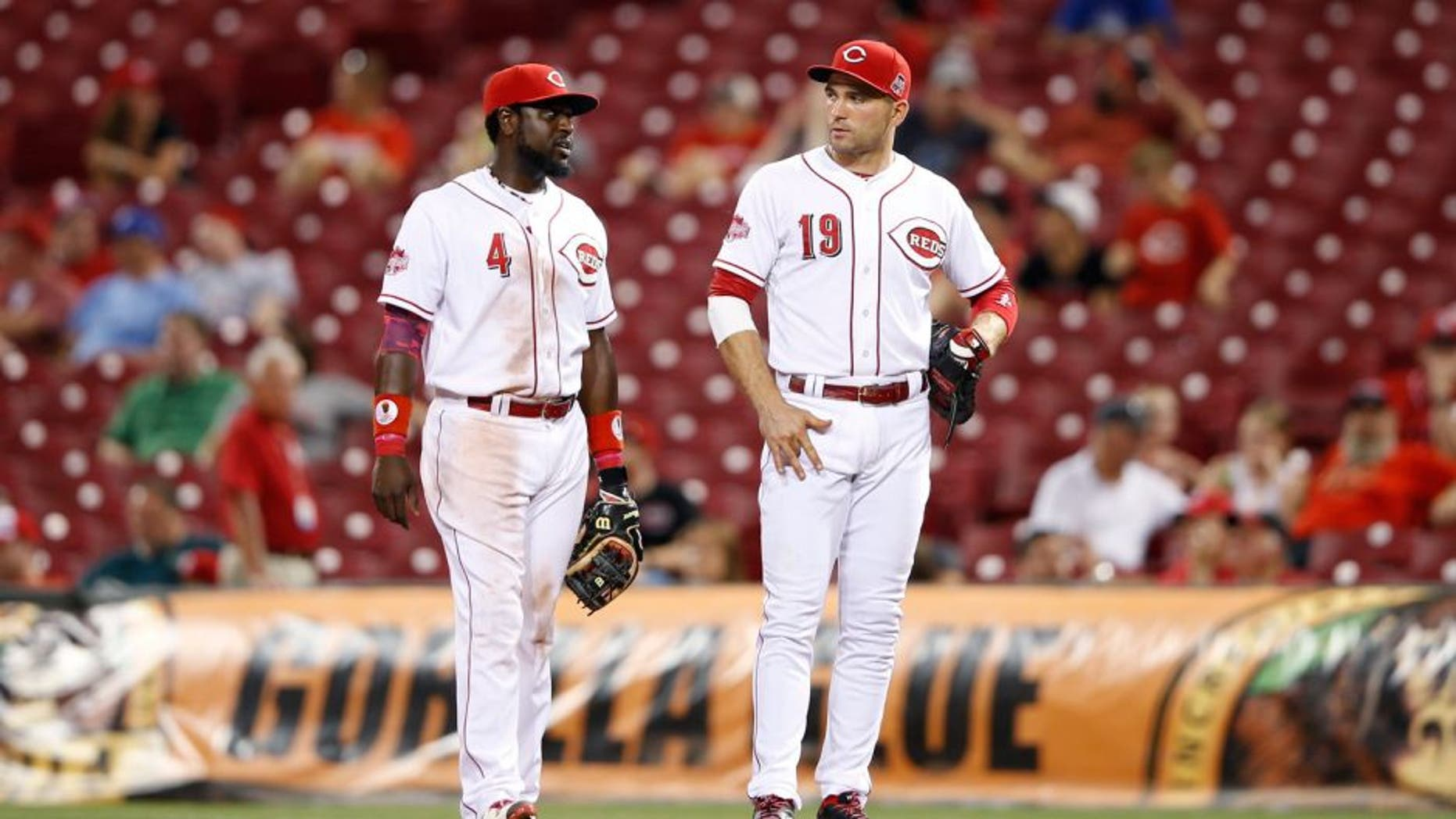 CINCINNATI, OH - AUGUST 18: Joey Votto #19 and Brandon Phillips #4 of the Cincinnati Reds look on against the Kansas City Royals during the game at Great American Ball Park on August 18, 2015 in Cincinnati, Ohio. The Royals defeated the Reds 3-1 in 13 innings. (Photo by Joe Robbins/Getty Images)