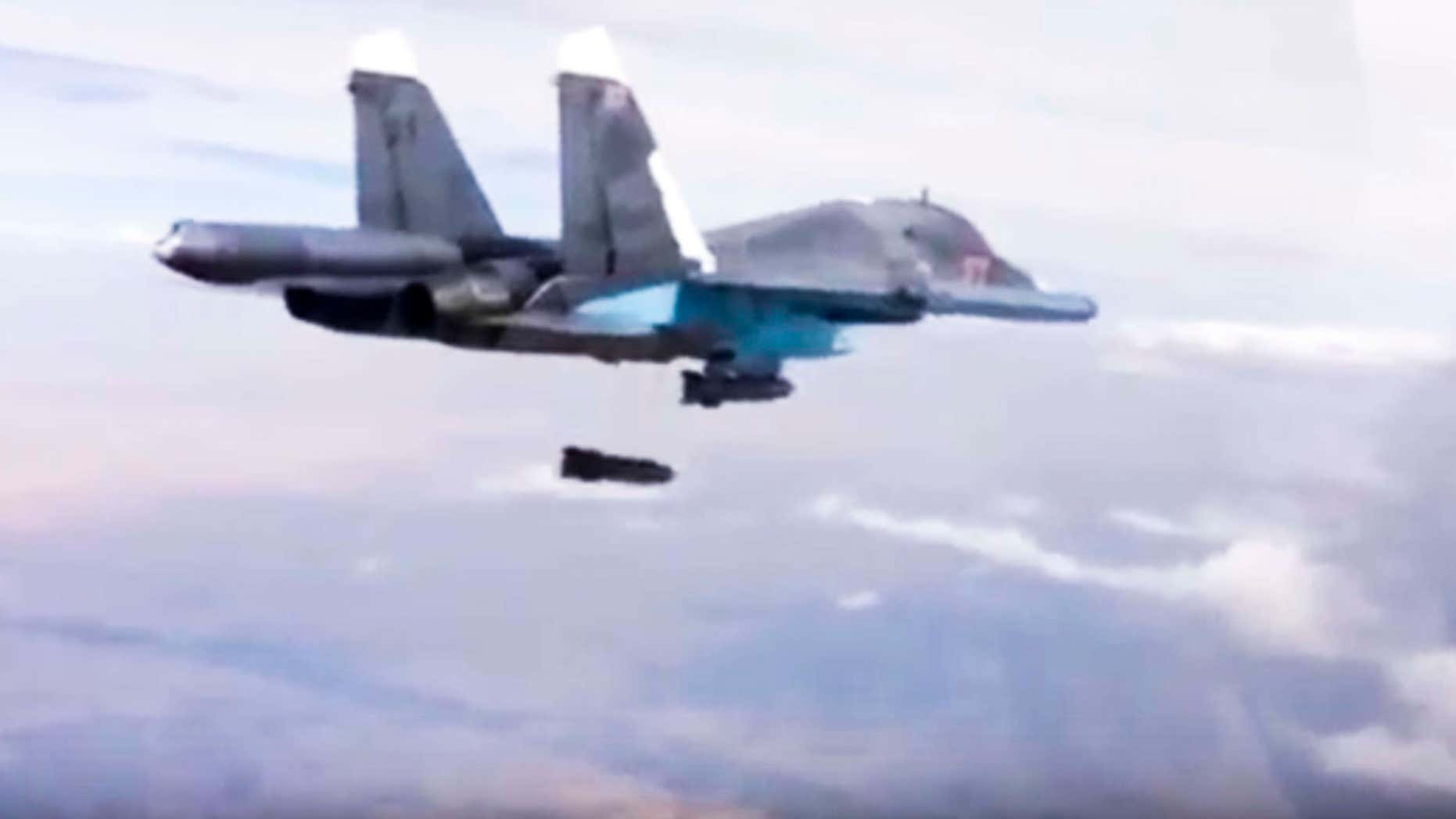 FILE - In this Dec. 9, 2015 file photo made from video footage provided by the Russian Defense Ministry, a Russian Su-34 bomber drops bombs on a target.
