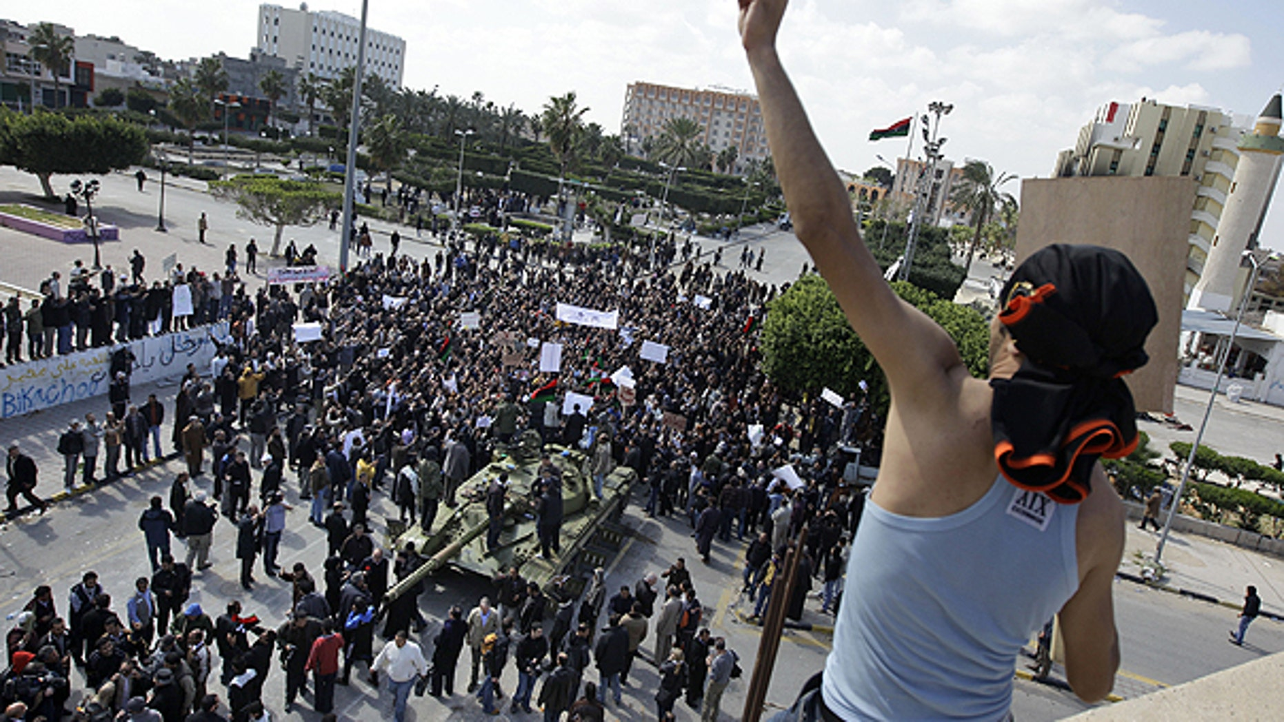 Feb. 27: Residents gather around a tank and an armed man on a rooftop flashes the victory sign, as foreign journalists arrive in Zawiya, 30 miles west of Tripoli, in Libya.