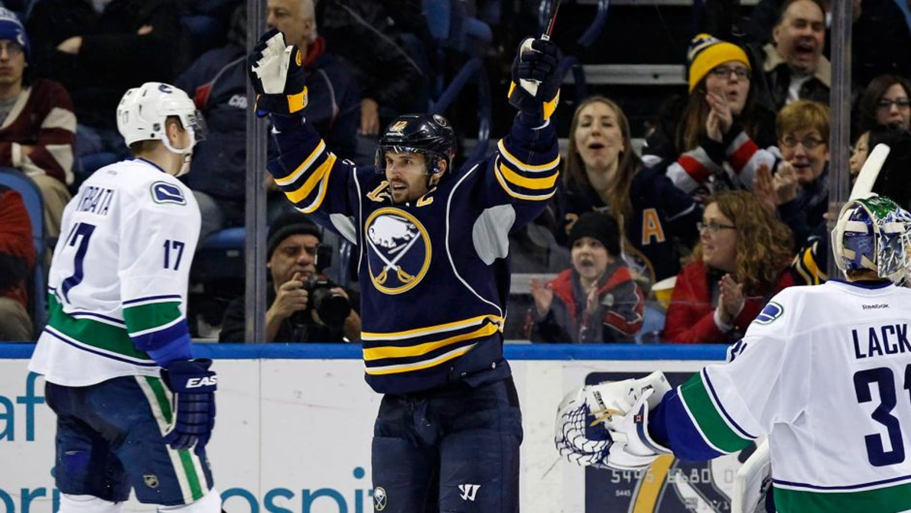Feb 26, 2015; Buffalo, NY, USA; Buffalo Sabres right wing Brian Gionta (12) celebrates the goal by defenseman Andrej Meszaros (41) (not shown) during the third period at First Niagara Center. Sabres beat the Canucks 6-3. Mandatory Credit: Kevin Hoffman-USA TODAY Sports