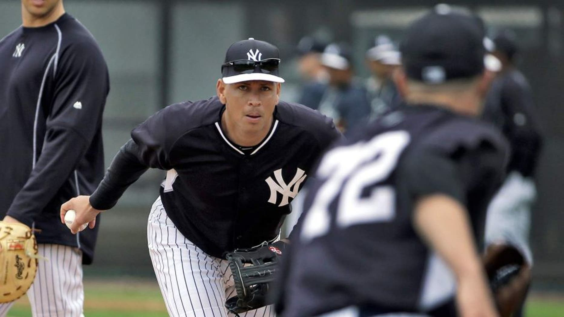 New York Yankees' Alex Rodriguez, center, flips the ball to pitcher Danny Burawa, right, as Mark Teixeira, left, looks on during workouts Friday, Feb. 27, 2015, in Tampa, Fla. Rodriguez was practicing at first base for the first time. (AP Photo/Chris O'Meara)