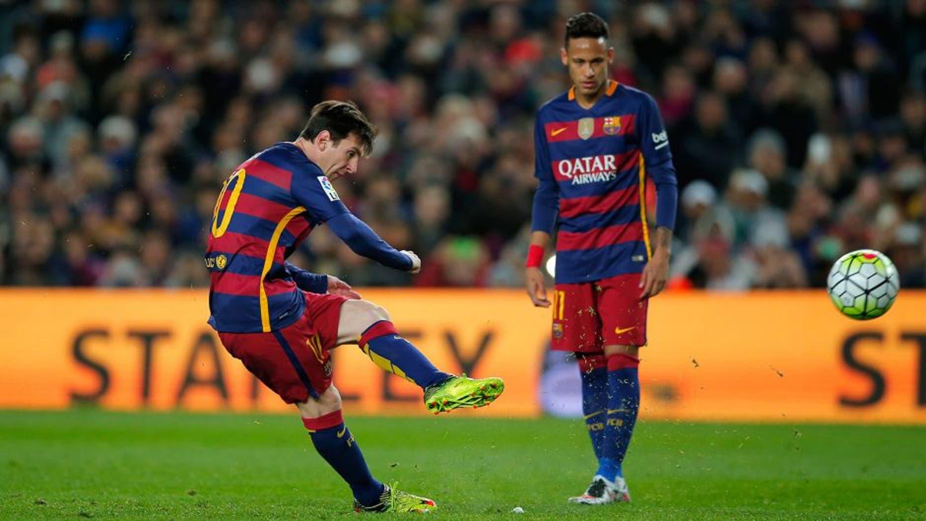 FC Barcelona's Lionel Messi, left, kicks the ball to score against Sevilla during a Spanish La Liga soccer match at the Camp Nou stadium in Barcelona, Spain, Sunday, Feb. 28, 2016. (AP Photo/Manu Fernandez)