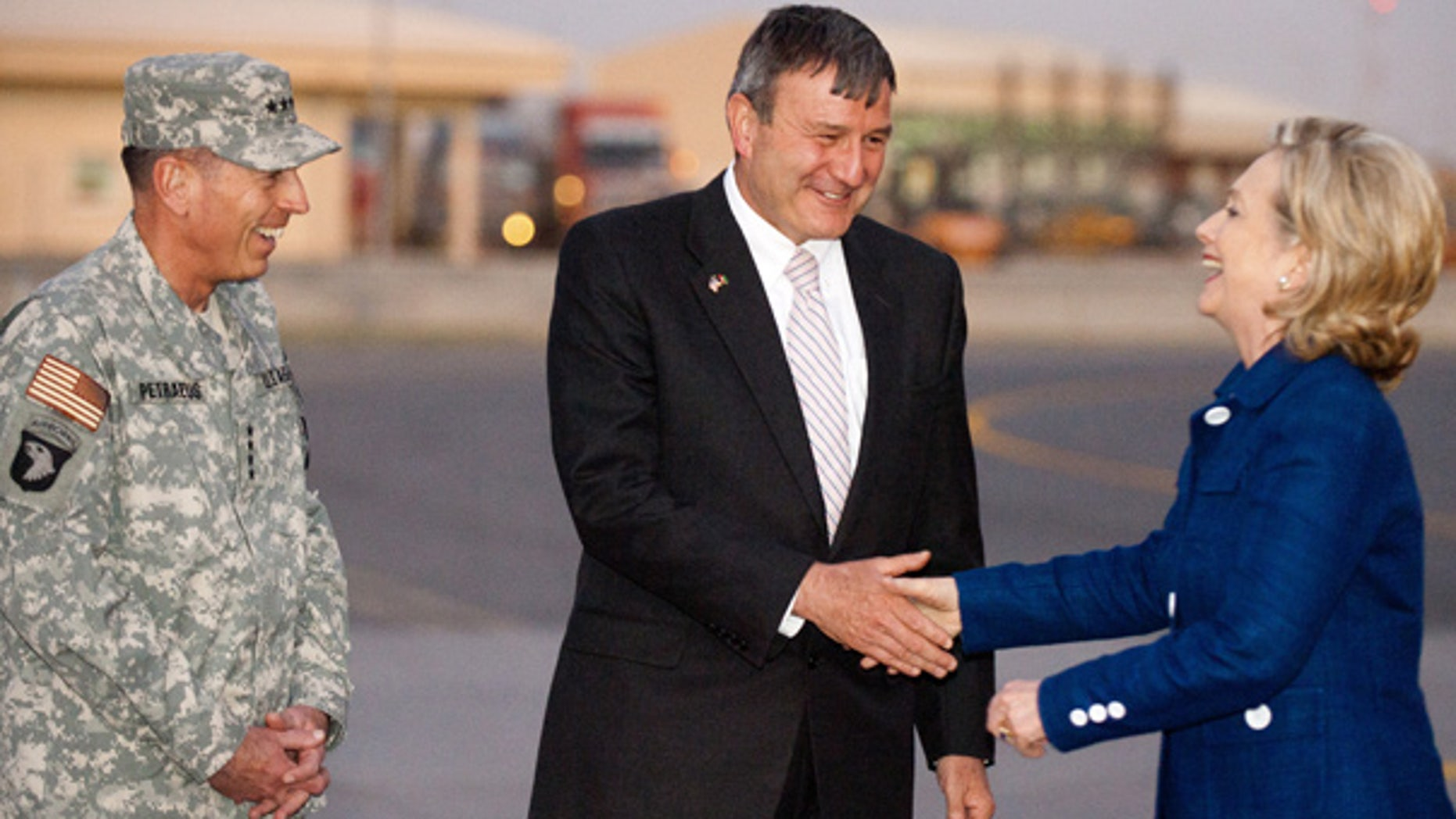 July 19: U.S. Ambassador to Afghanistan Karl Eikenberry, center, and General David Petraeus, left, greet Secretary of State Hillary Clinton as she steps off her plane at Kabul International Airport.