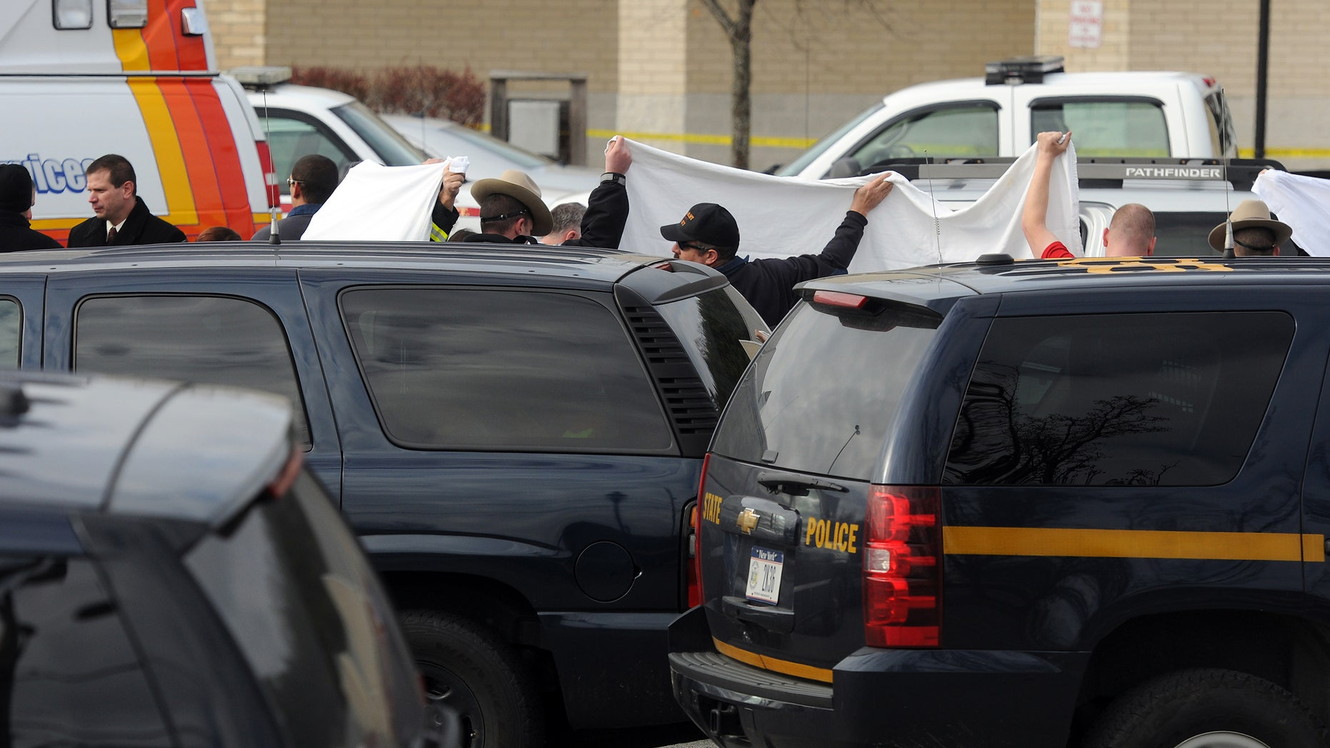 In this photo taken on Thursday, Nov. 21, 2013, State police investigate near a vehicle in a supermarket parking lot in Pleasant Valley, N,Y., where 49-year-old pharmacist Abbas Lodhi and one of sons were found shot dead. Police say they later found the body of the man's other son at the family's nearby home. Police are continuing to search for the man's 43-year-old wife Sarwat Lodhi, who is missing and has unspecified injuries. They describe her as a victim in the case. (AP Photo/The Journal, Darryl Bautista) NO SALES. MIDDLETOWN OUT, KINGSTON OUT.