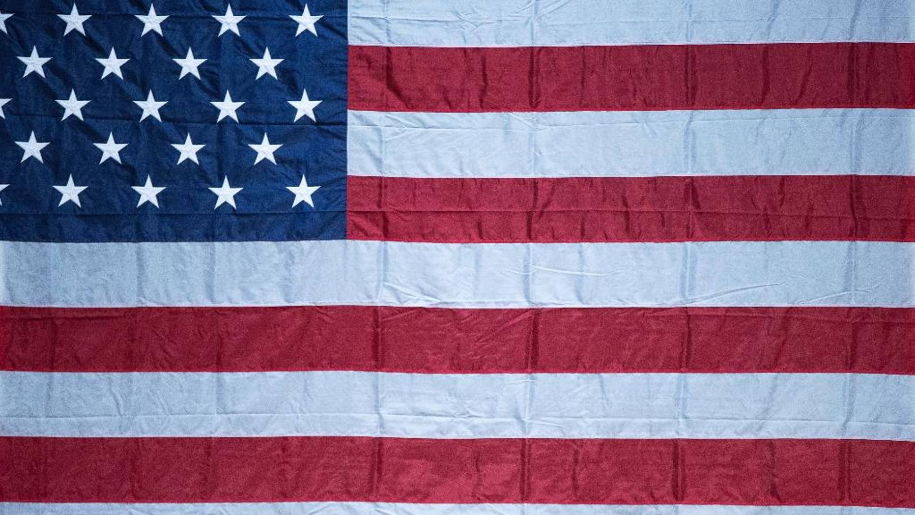 A man sticks his head out from under a large American flag as Democratic presidential candidate Hillary Clinton finishes a rally at Miami Dade College in Miami, Tuesday, Oct. 11, 2016. (AP Photo/Andrew Harnik)