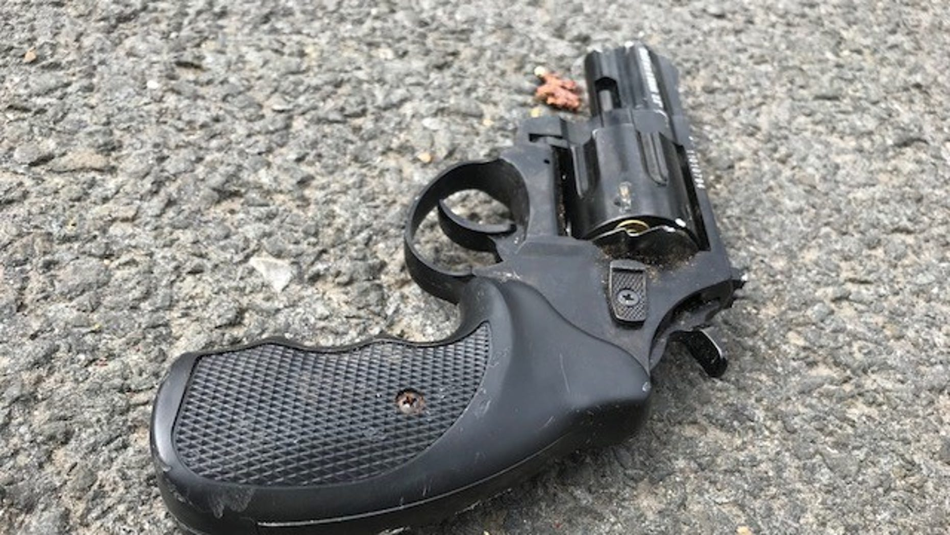 A woman with a gun was shot in the arm after a weekend of bizarre behavior and crimes, reports say.