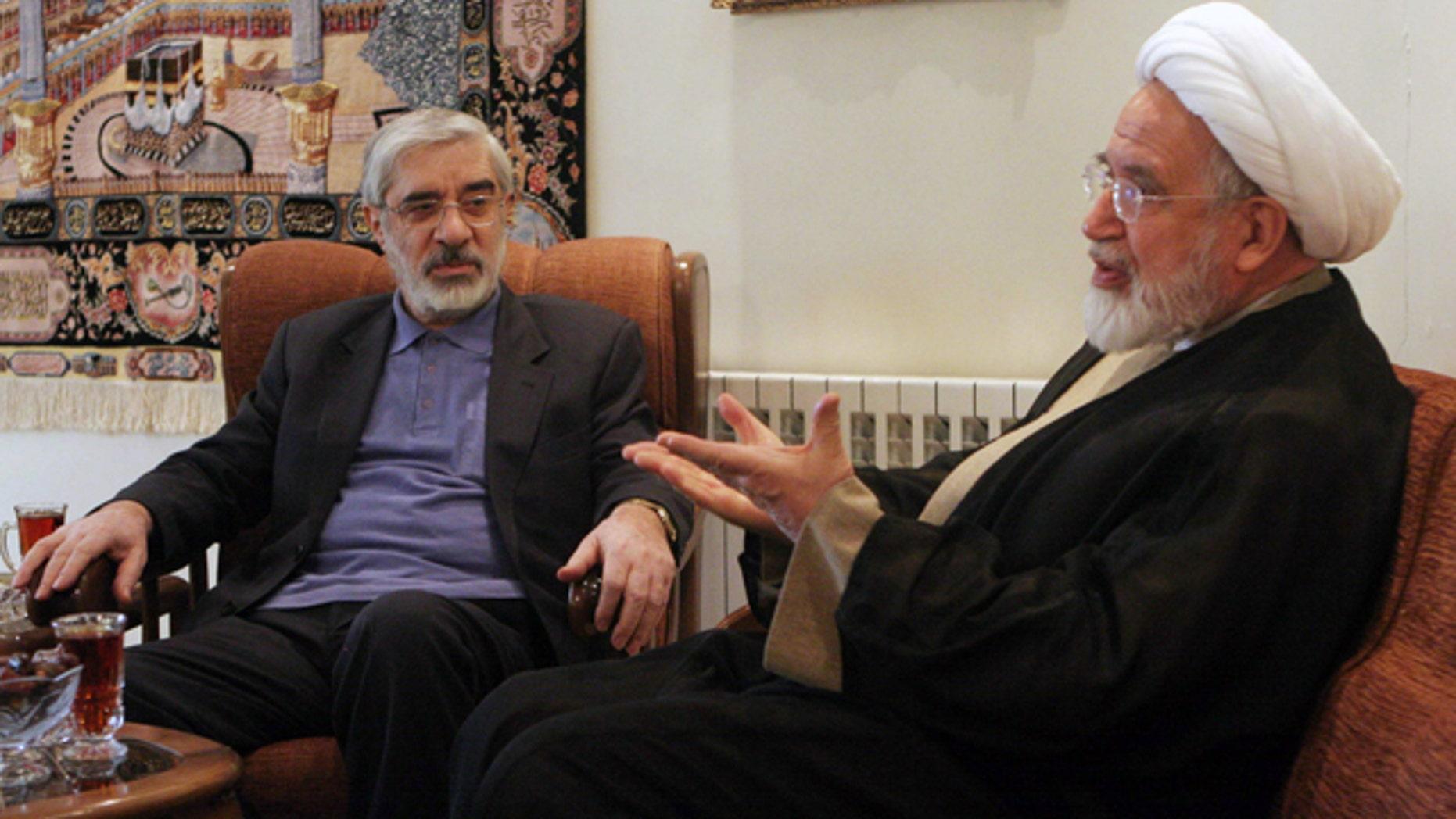 In this Saturday, Oct. 10, 2009, file photo, leaders of Iranian opposition, Mahdi Karroubi, right, and Mir Hossein Mousavi talk in Tehran, Iran.
