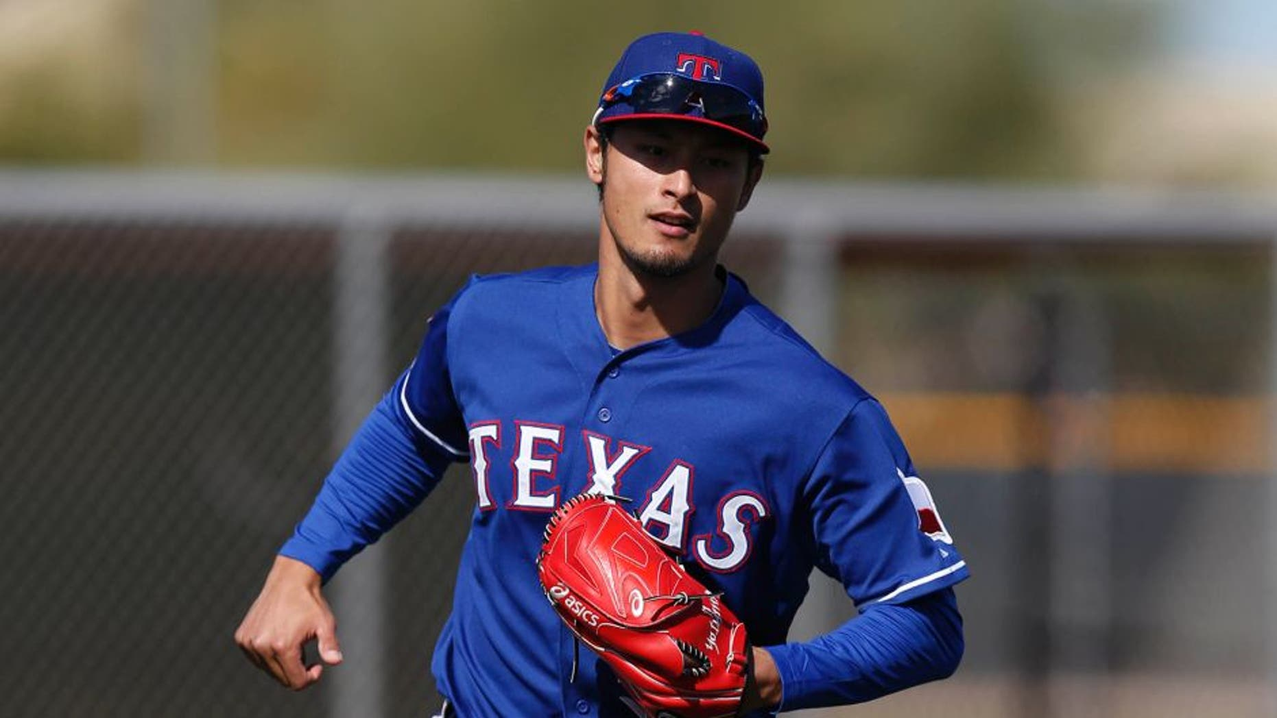 Feb 24, 2015; Surprise, AZ, USA; Texas Rangers starting pitcher Yu Darvish (11) fields grounders during spring training camp at Surprise Stadium. Mandatory Credit: Rick Scuteri-USA TODAY Sports