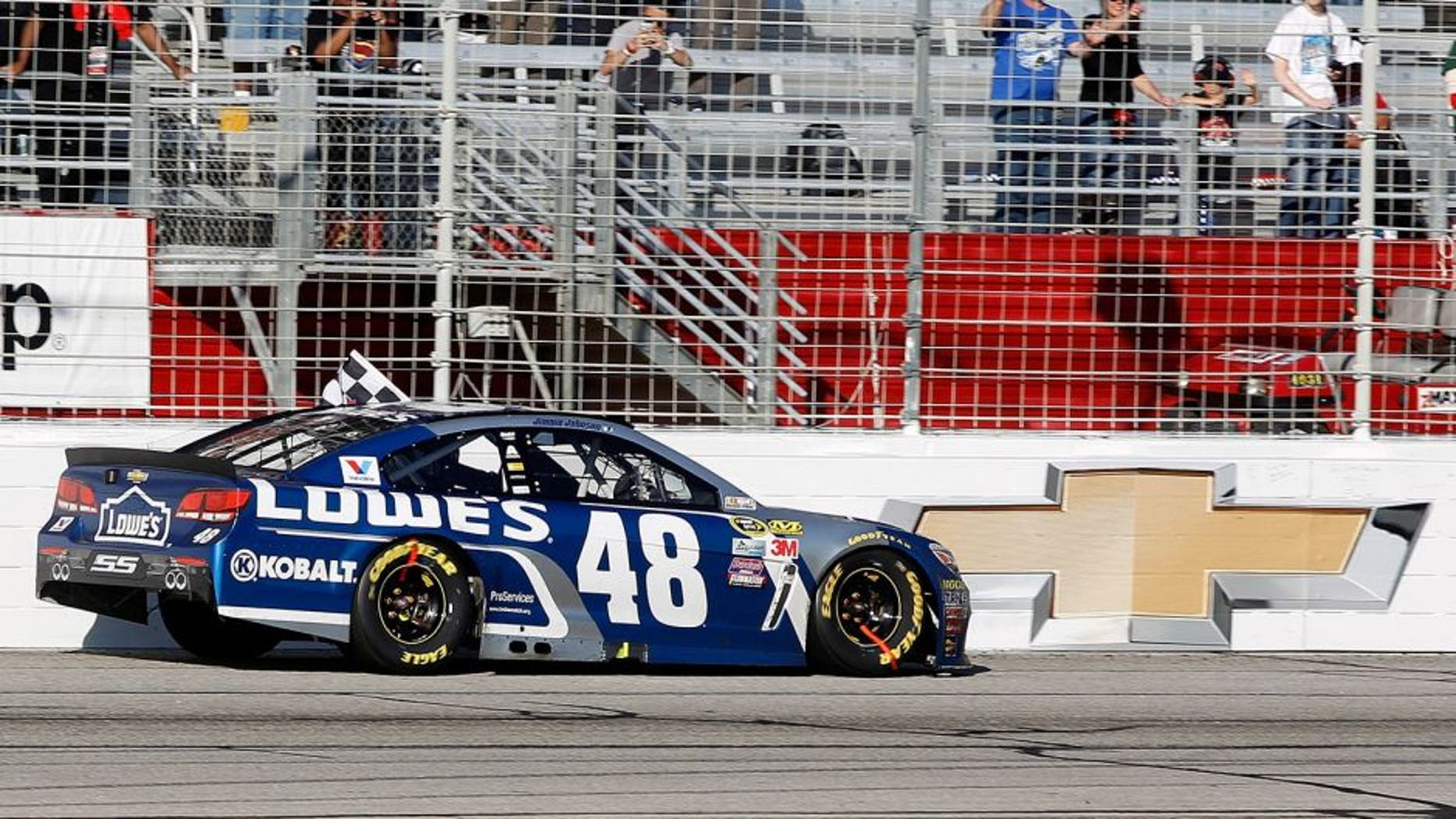 HAMPTON, GA - FEBRUARY 28: Jimmie Johnson, driver of the #48 Lowe's Chevrolet, celebrates with the checkered flag after winning the NASCAR Sprint Cup Series Folds of Honor QuikTrip 500 at Atlanta Motor Speedway on February 28, 2016 in Hampton, Georgia. (Photo by Brian Lawdermilk/Getty Images)