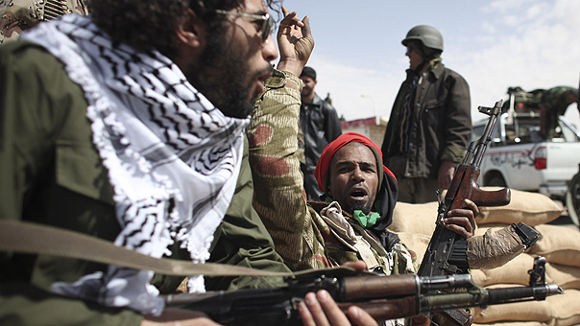 March 3: Defected Libyan soldiers and volunteers cheer as they sit on the outskirts of the eastern town of Brega, Libya.