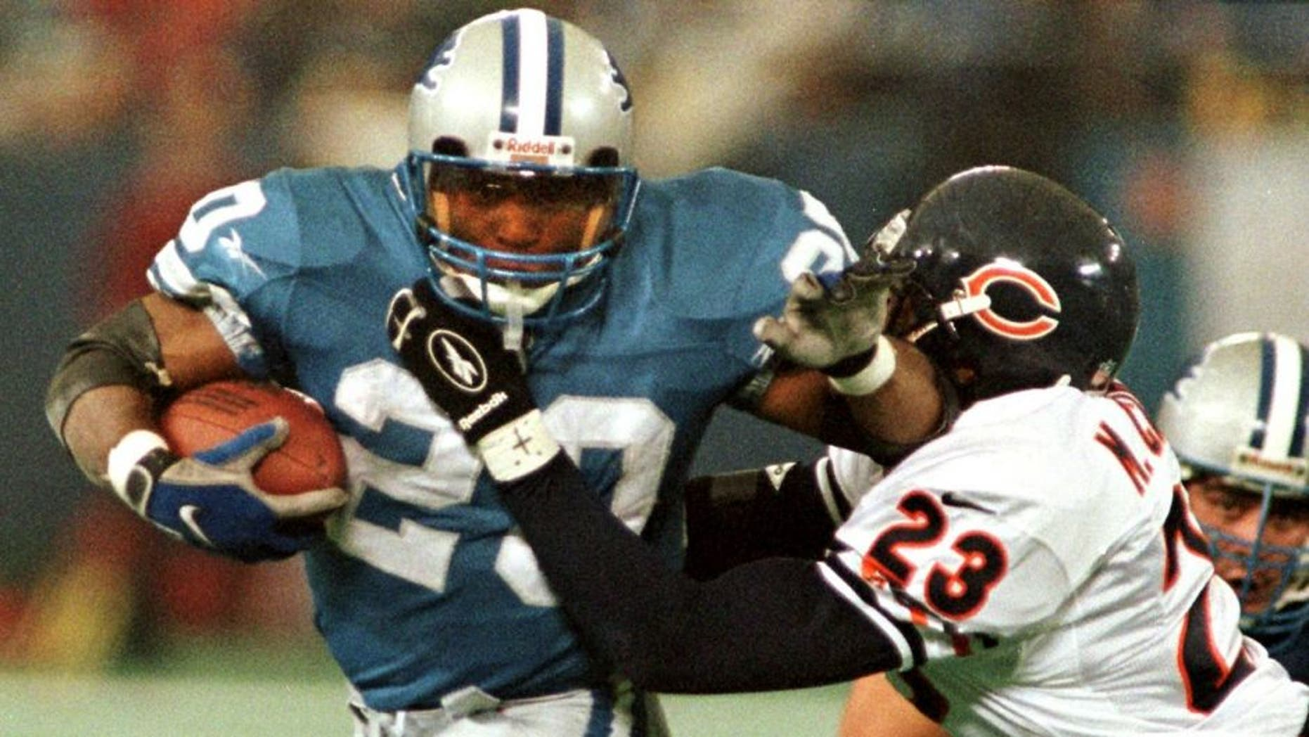 PONTIAC, : The Detroit Lions' Barry Sanders (L) brushes off Chicago Bears safety Marty Carter (R) on his way to the end zone for a touchdown in the third quarter, 27 November, at the Silverdome in Pontiac, MI. On the play, Sanders passed the 100-yard mark in a game for the 11th straight time tieing the NFL record held by Marcus Allen. The Lions beat the Bears 55-20. AFP PHOTO Matt CAMPBELL (Photo credit should read MATT CAMPBELL/AFP/Getty Images)