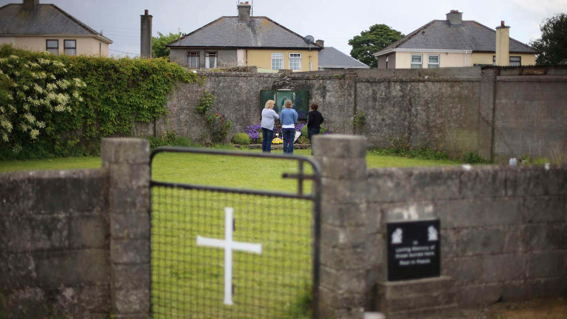FILE In this June 7, 2014 file photo members of the public at the site of a mass grave for children who died in the Tuam mother and baby home, in Tuam, County Galway.