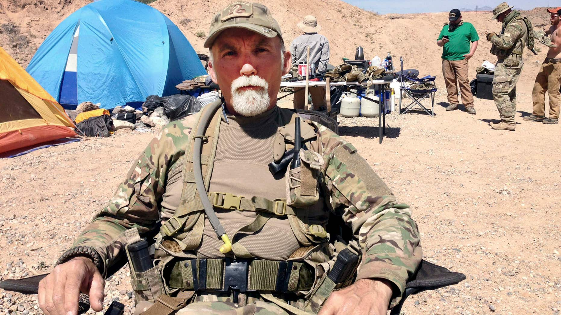 FILE - In this April 16, 2014 file photo, Jerry DeLemus, of Rochester, N.H., sits with a group of self-described militia members camping on rancher Cliven Bundy's ranch near Bunkerville, Nev.