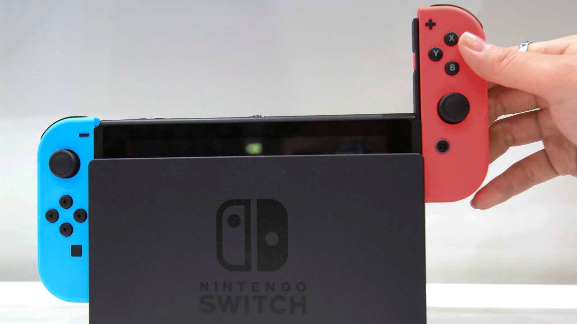 FILE - In this Friday, Jan. 13, 2017, file photo, a model puts the controller onto the Nintendo Switch during a presentation event of the new Nintendo Switch in Tokyo.