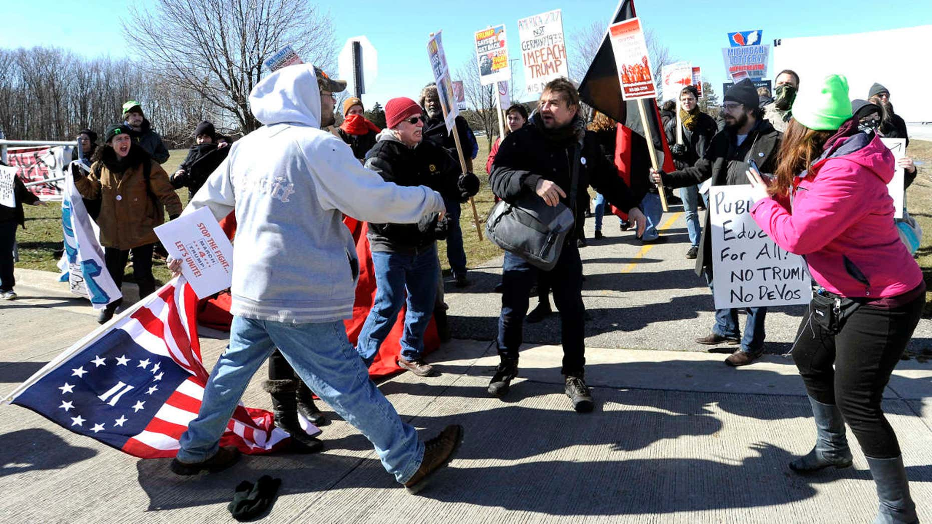 March 4, 2017: Trump supporters, left, and protestors, right, briefly push and shove each other after a woman was allegedly hit and a sign thrown on the ground during a rally in support of President Donald Trump at Freedom Hill County Park in Sterling Heights, Mich.