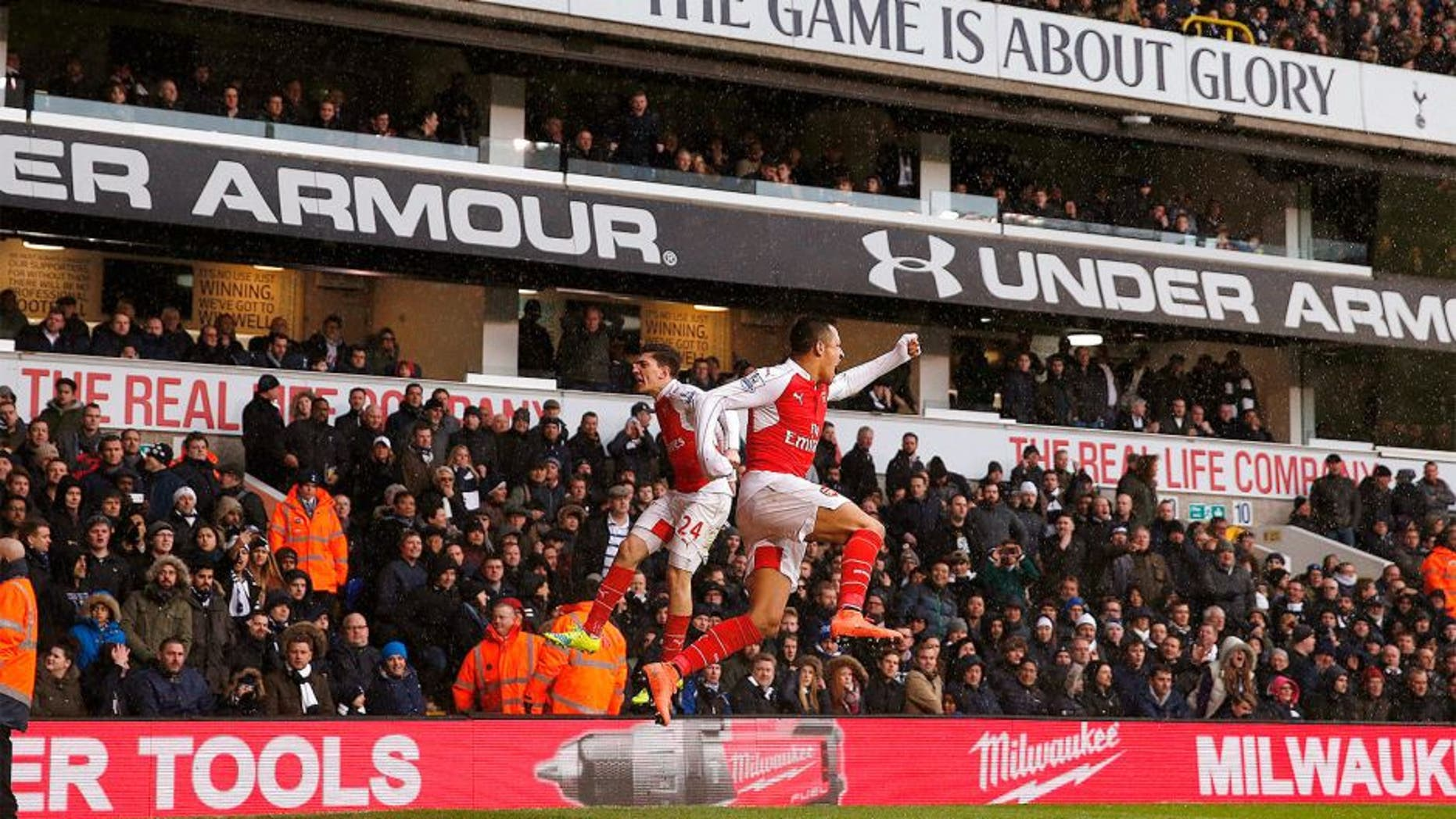 Arsenal's Chilean striker Alexis Sanchez (R) celebrates with Arsenal's Spanish defender Hector Bellerin (L) after scoring their second goal during the English Premier League football match between Tottenham Hotspur and Arsenal at White Hart Lane in London, on March 5, 2016. / AFP / ADRIAN DENNIS / RESTRICTED TO EDITORIAL USE. No use with unauthorized audio, video, data, fixture lists, club/league logos or 'live' services. Online in-match use limited to 75 images, no video emulation. No use in betting, games or single club/league/player publications. / (Photo credit should read ADRIAN DENNIS/AFP/Getty Images)