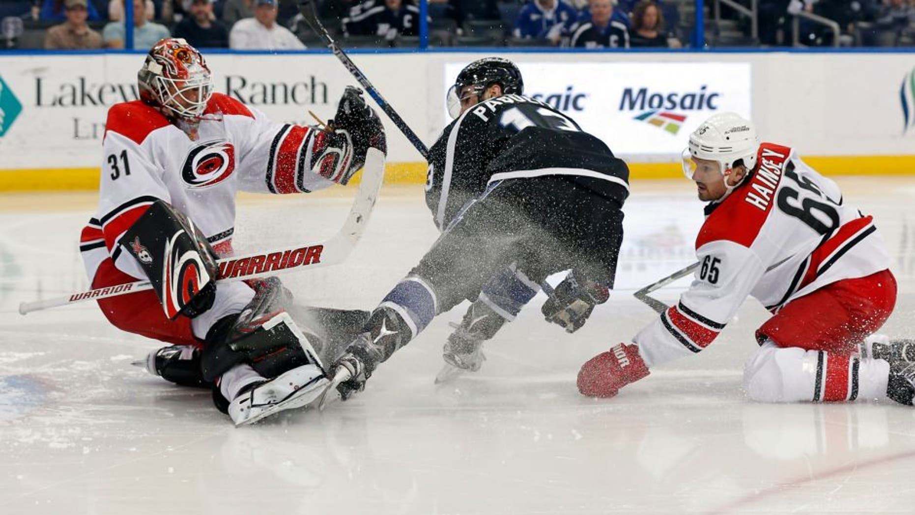 Carolina Hurricanes goalie Eddie Lack (31), of Sweden, makes a save on Tampa Bay Lightning's Cedric Paquette, as Hurricanes' Ron Hainsey defends during the second period of an NHL hockey game Saturday, March 5, 2016, in Tampa, Fla. (AP Photo/Mike Carlson)