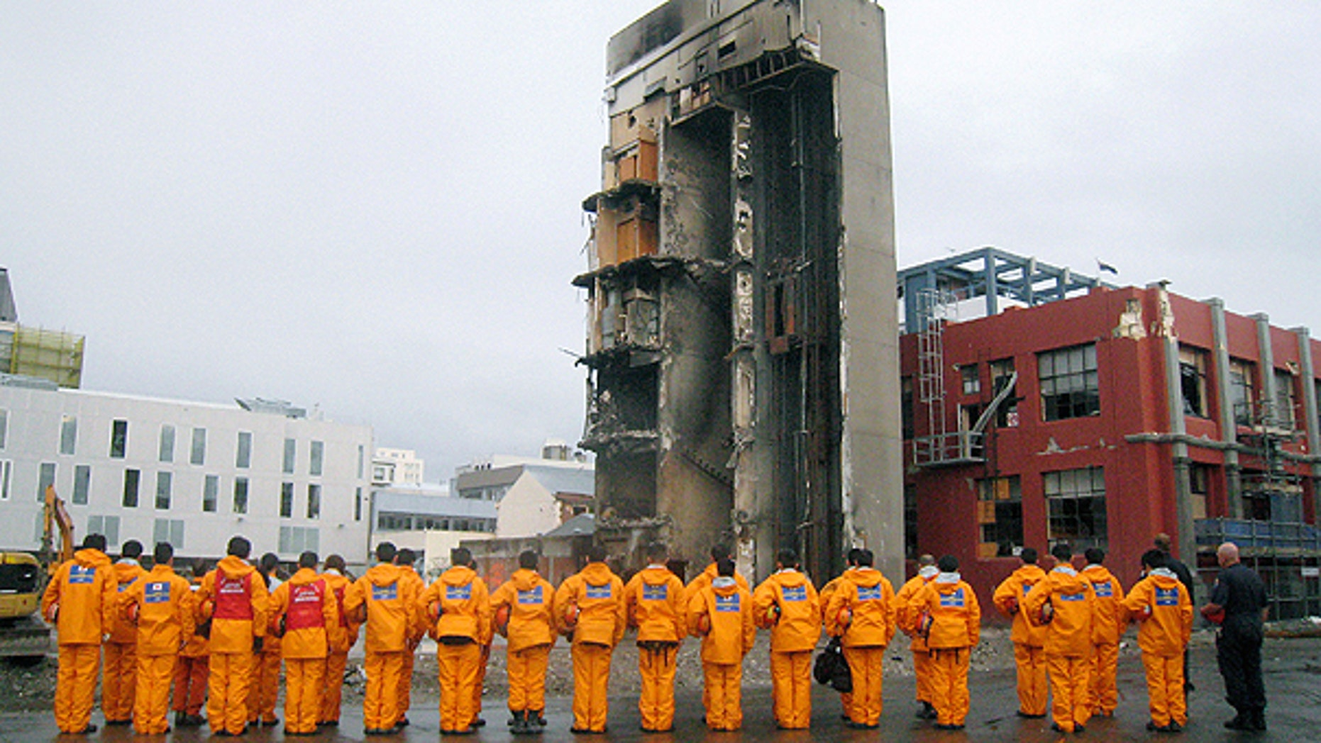 March 6: In this photo released by Japan Disaster Relief Team, its members observe a moment of silence near at the collapsed CTV building in Christchurch, New Zealand.