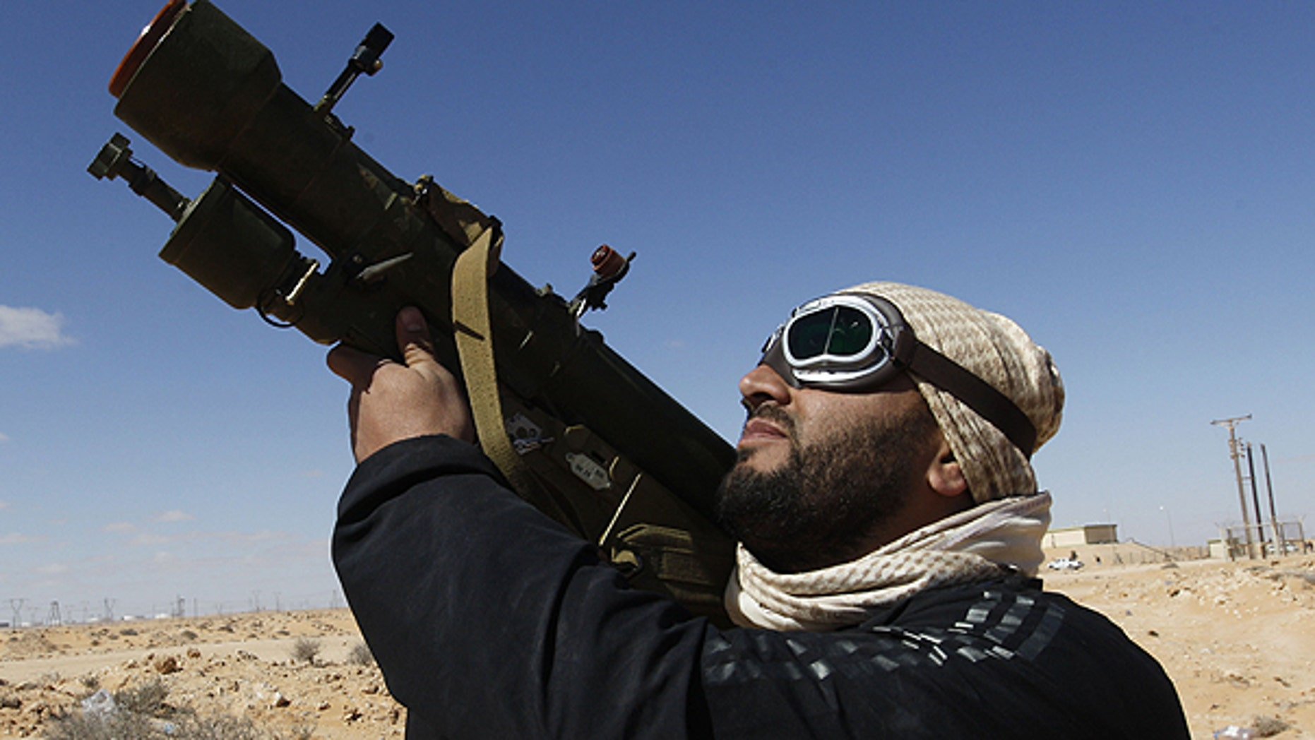 March 6: An rebel against Libyan leader Muammar Qaddafi holds his anti-aircraft missile as he looks to the sky, in the oil town of Ras Lanouf, eastern Libya.