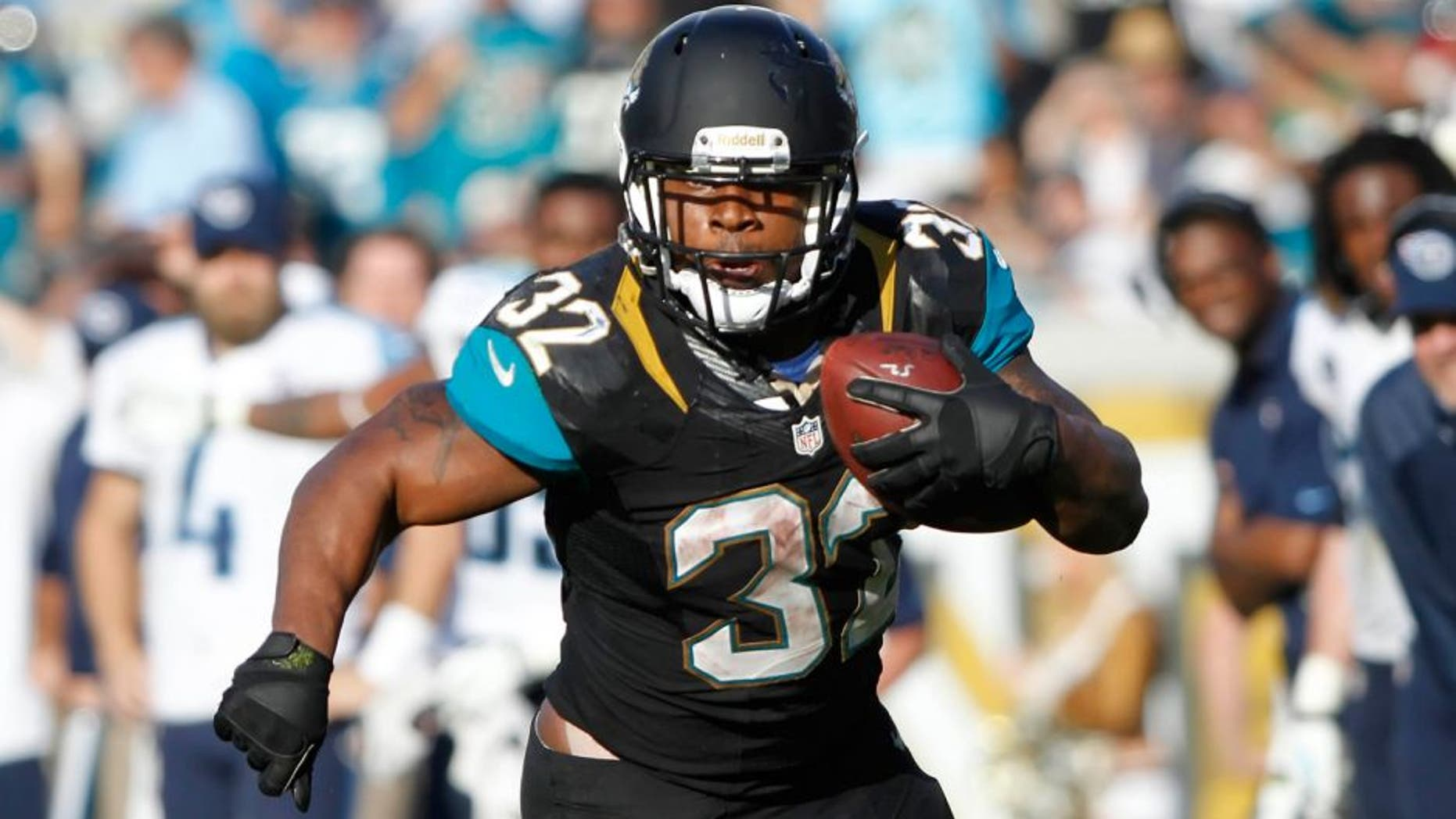 Dec 22, 2013; Jacksonville, FL, USA; Jacksonville Jaguars running back Maurice Jones-Drew (32) runs with the ball as Tennessee Titans defends during the second half at EverBank Field. Tennessee Titans defeated the Jacksonville Jaguars 20-16. Mandatory Credit: Kim Klement-USA TODAY Sports